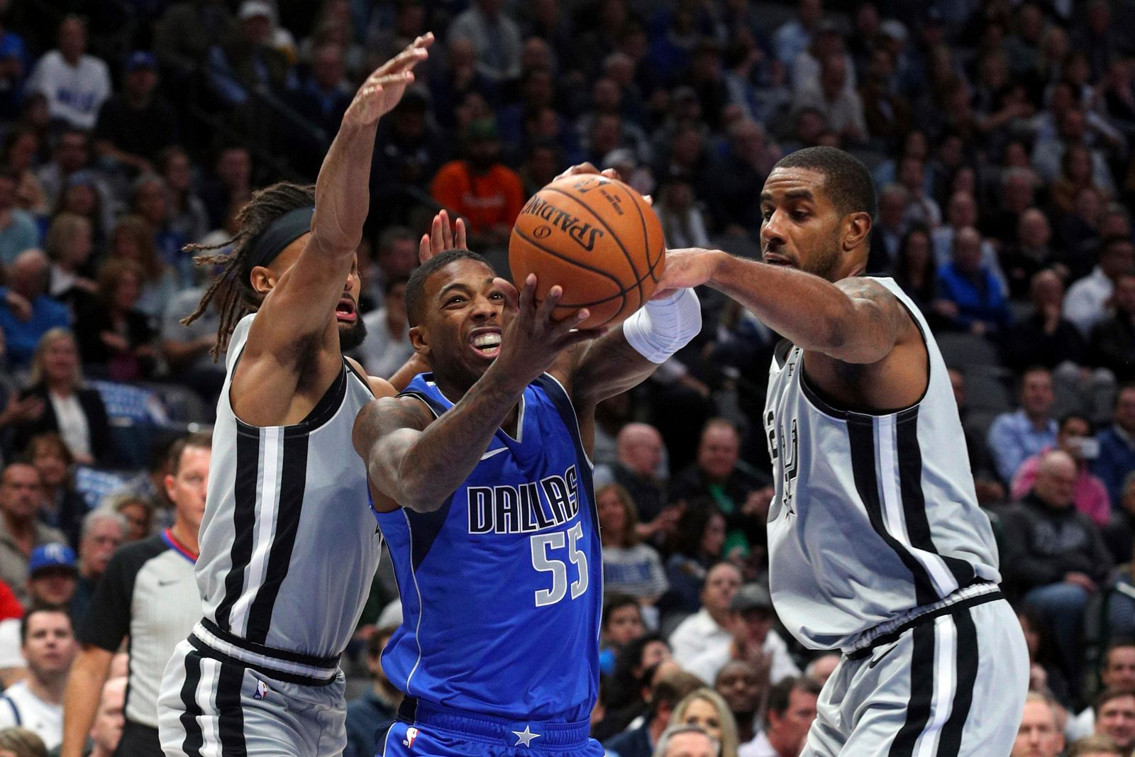Dallas Mavericks guard Delon Wright (55) tries to drive the ball between San Antonio Spurs guard Patty Mills (8) and San Antonio Spurs center LaMarcus Aldridge (12) in the first half in an NBA basketball game Monday, Nov. 18, 2019, in Dallas. (AP Photo/Richard W. Rodriguez)