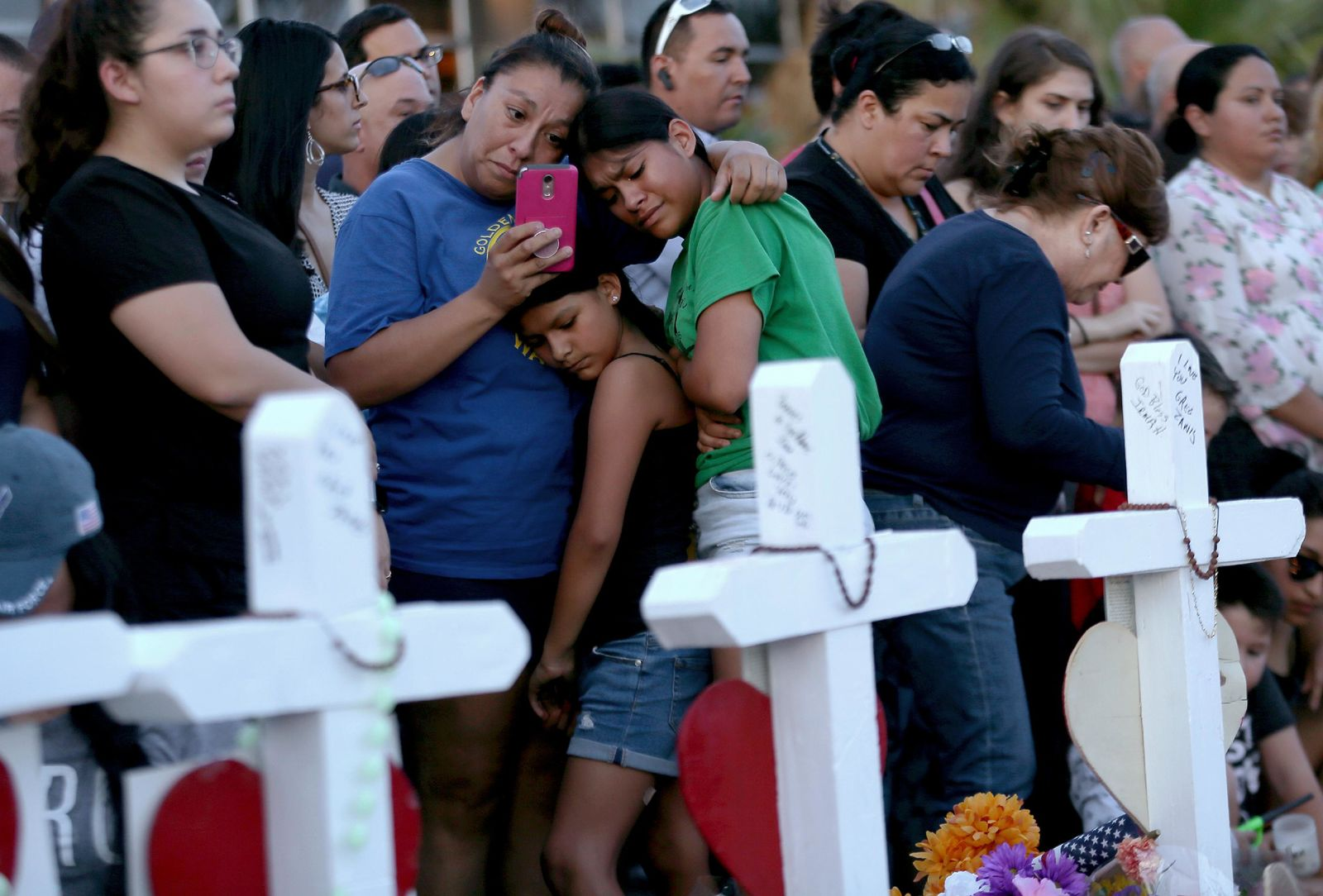 A mother clings to her daughters as they visit a memorial for the victims of Saturday's mass shooting, outside the Walmart Monday, Aug. 5, 2019, in El Paso, Texas. (Mark Lambie/The El Paso Times via AP)