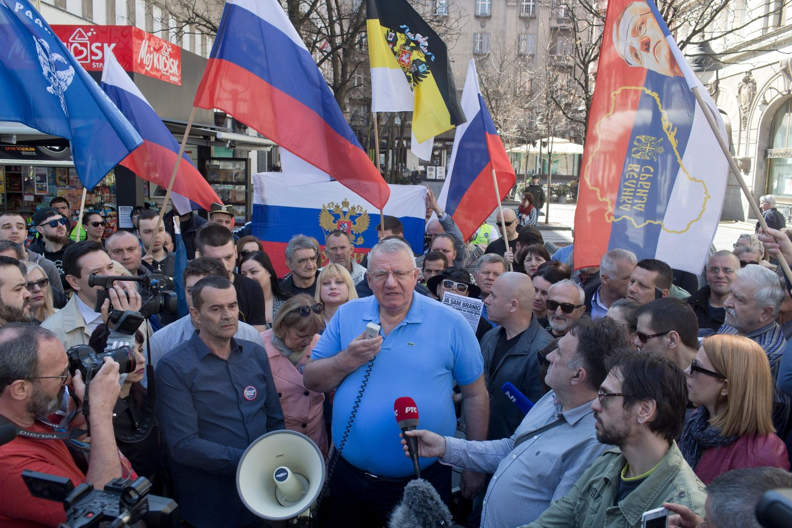 Vojislav Seselj, center, the leader of the ultranationalist Serbian Radical Party, speaks to his supporters over a megaphone during a protest in Belgrade, Serbia, Sunday, March 24, 2019.{ } (AP Photo/Marko Drobnjakovic)