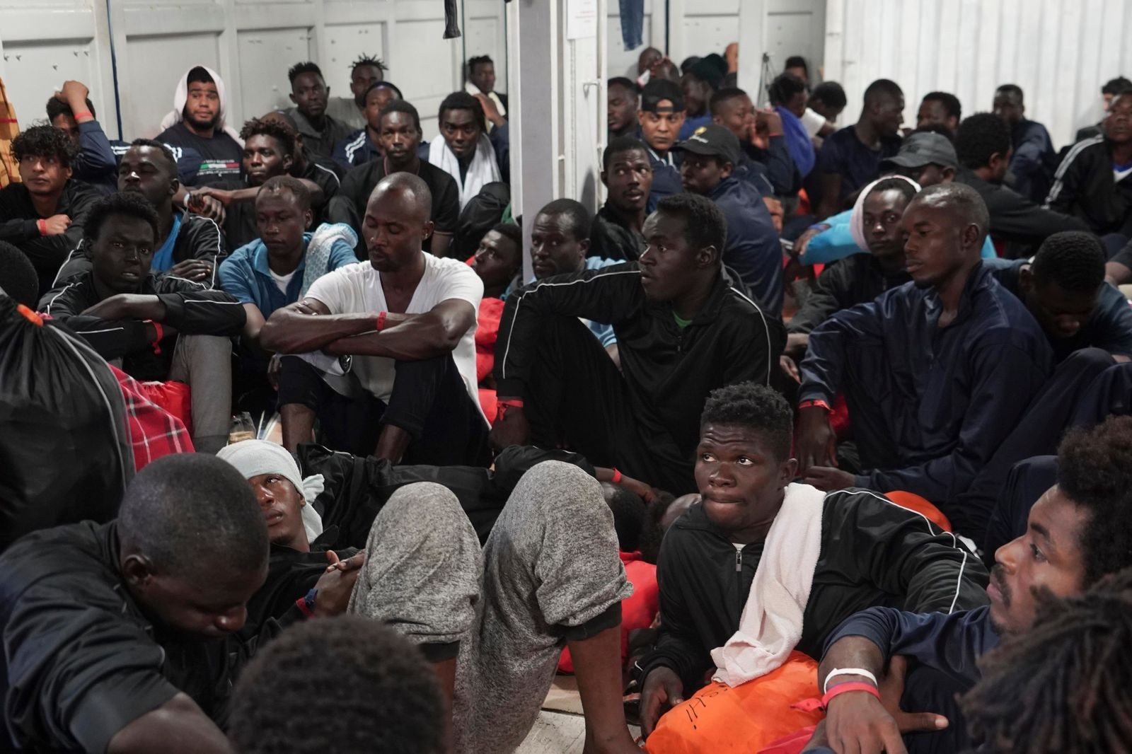 Men gather during a question and answer session with representatives of SOS Mediterranee and Doctors Without Borders in the men's shelter aboard the Ocean Viking in the Mediterranean Sea, Sunday, Sept. 22, 2019. The humanitarian ship carrying 182 people in international waters is sailing back and forth between Italy and Malta as it waits for European governments to allow it in. (AP Photo/Renata Brito)