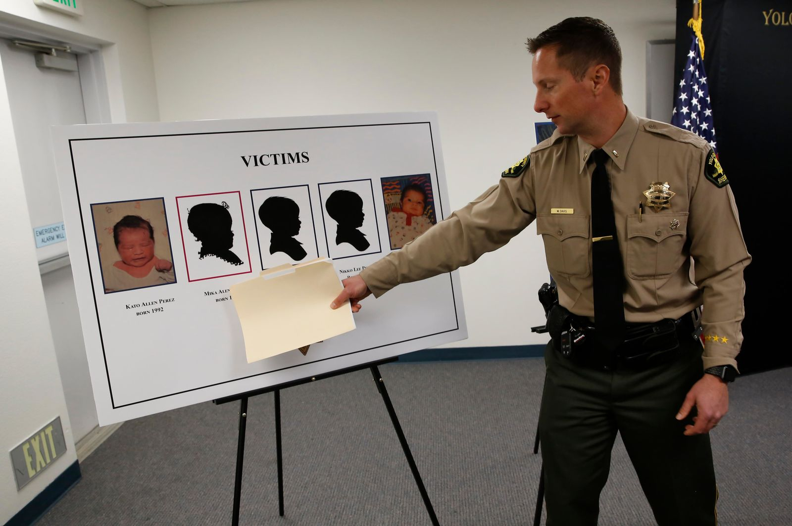 Lieutenant Matthew Davis of the Yolo County Sheriff's Department gestures to the images of five infants believed to be killed by their father, during a news conference in Woodland, Calif., Monday, Jan. 27, 2020. Paul Perez, 57, has been arrested in the decades-old killings of five of his infant children, a case the sheriff said had haunted his agency for years, the Yolo County Sheriff's Office said Monday, Jan. 27, 2020. (AP Photo/Rich Pedroncelli)