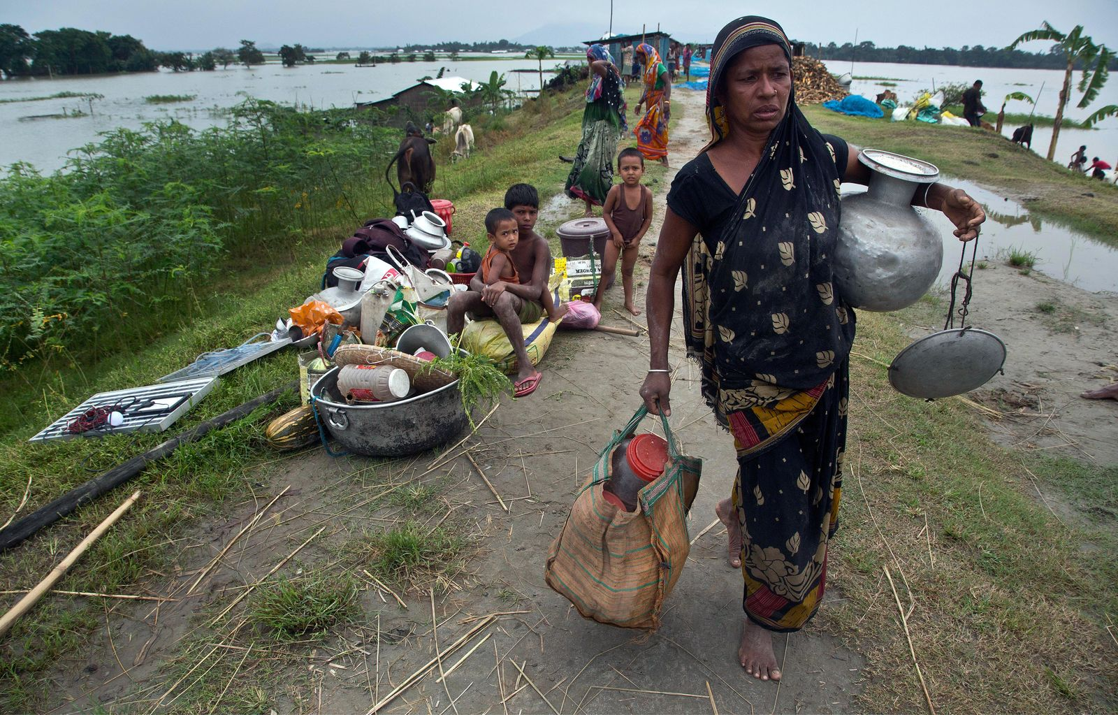 An Indian flood affected woman carries her belongings on an embankment to take shelter in Pabhokathi village east of Gauhati India, Monday, July 15, 2019. .(AP Photo/Anupam Nath)