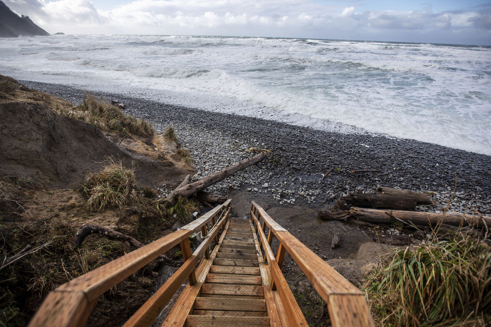 In this Sunday, Jan. 12, 2020 photo, stairs lead down to Falcon Cove Beach between the unincorporated community of Arch Cape to the north and Oswald West State Park to the south in Clatsop County, Ore. A 7-year-old girl is dead and her 4-year-old brother is missing after they and their father were swept into the ocean on the Oregon coast amid a high-surf warning. Authorities say the father was holding the two children when a wave swept all three into the water Saturday, Jan. 11 in the Falcon Cove area, south of the community of Cannon Beach. (Mark Graves/The Oregonian via AP)