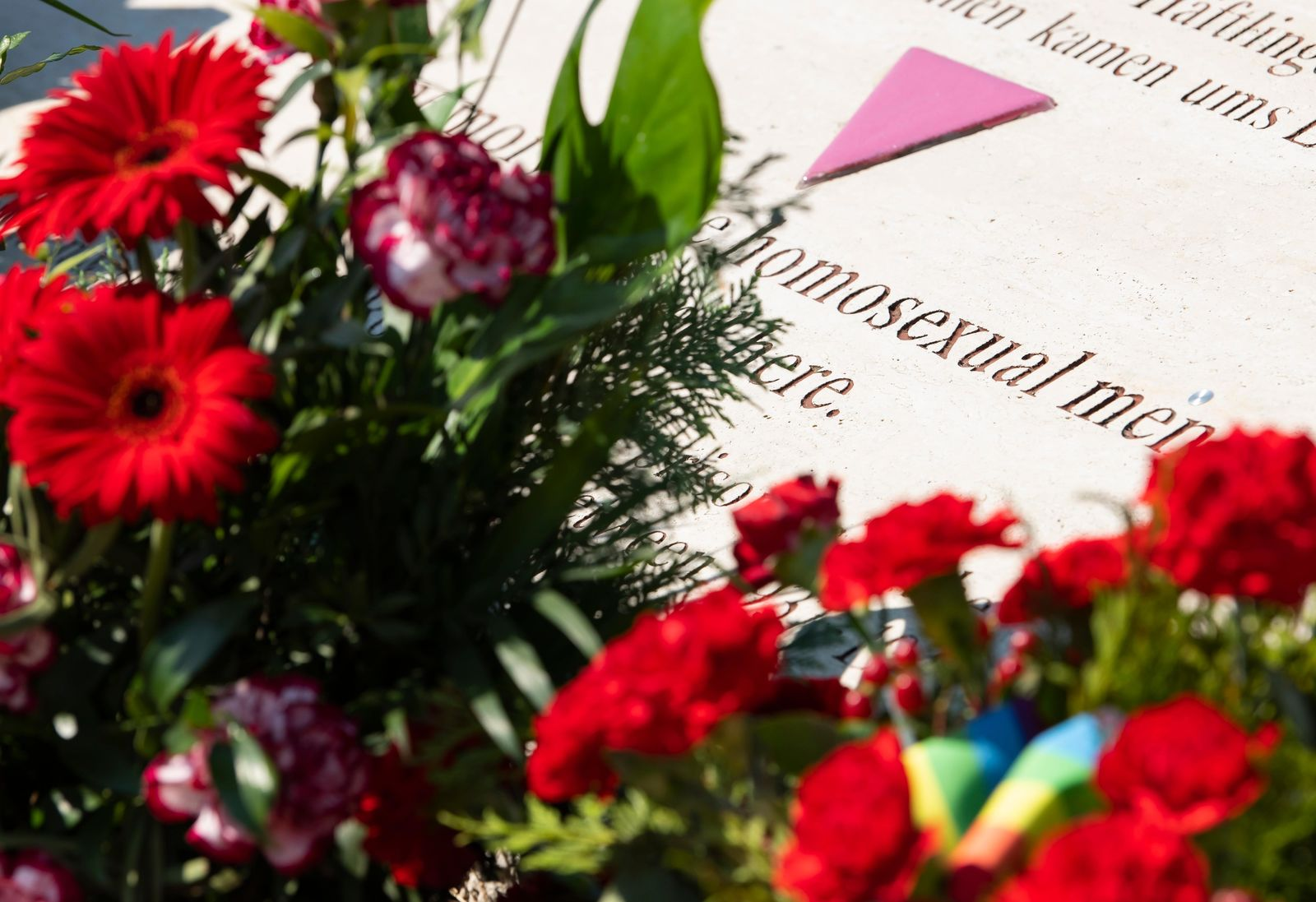 Flowers are placed at a memorial stone in remembrance for prisoners assigned a pink triangle in the former Nazi concentration camp Buchenwald within the Christopher Street Day in Weimar, Germany, Sunday, June 23, 2019. There were 650 prisoners assigned a pink triangle in the Buchenwald concentration camp between 1937 and 1945. Many of them lost their lives. (AP Photo/Jens Meyer)