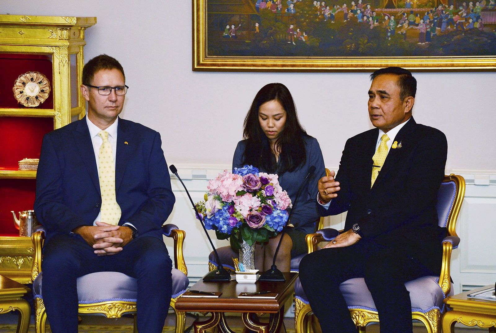In this photo released by Government Spokesman Office, Richard Harris, left, an Australian member of the Thai cave rescue team, listens to Thailand's Prime Minister Prayuth Chan-ocha, right, during a meeting after receiving the Member of the Most Admirable Order of the Direkgunabhorn during the royal decoration ceremony at the Royal Thai Government House in Bangkok, Thailand, Friday, April 19, 2019. (Government Spokesman Office via AP)