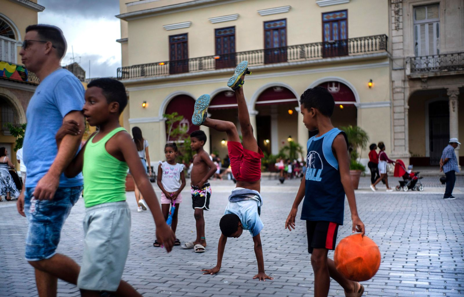 In this Nov. 10, 2019 photo, a youth does hand stands amid pedestrians in a square in Old Havana, Cuba. The city will celebrate its 500th anniversary on Nov. 16. (AP Photo/Ramon Espinosa)