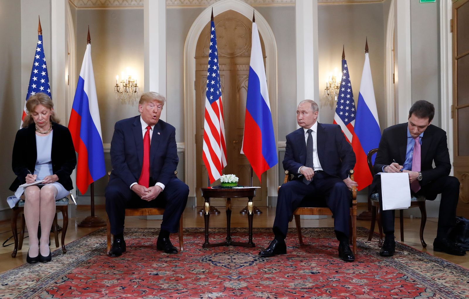 U.S. President Donald Trump, second from left, gives a statement as Russian President Vladimir Putin, second from right, looks on and translators take notes at the beginning of a meeting at the Presidential Palace in Helsinki, Finland, Monday, July 16, 2018. (AP Photo/Pablo Martinez Monsivais)