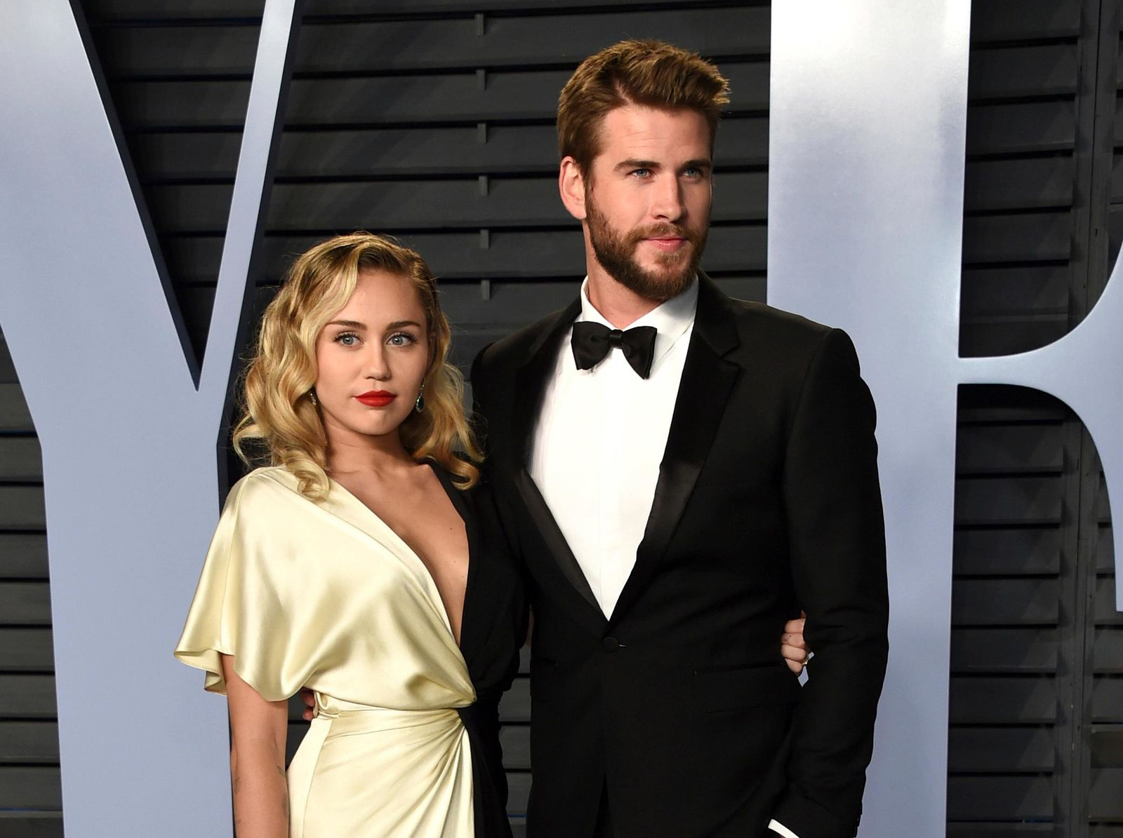 FILE - In this March 4, 2018 file photo, Miley Cyrus, left, and Liam Hemsworth arrive at the Vanity Fair Oscar Party in Beverly Hills, Calif.{ } (Photo by Evan Agostini/Invision/AP, FIle)