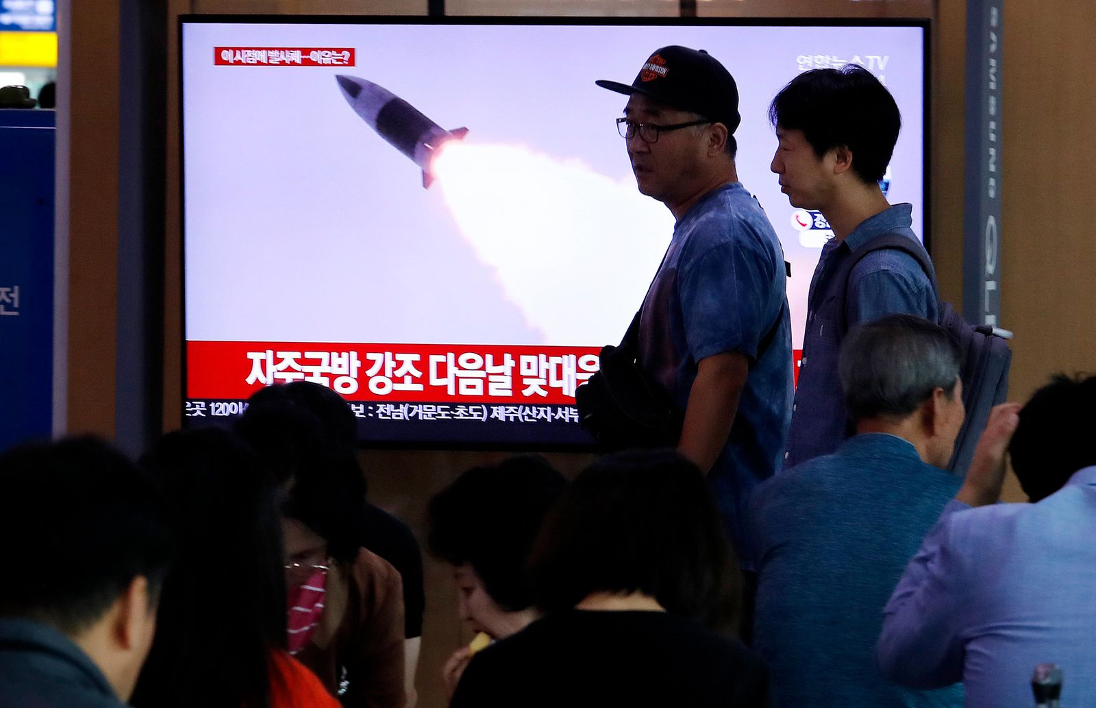 "People pass by a TV showing a file image of North Korea's missile launch during a news program at the Seoul Railway Station in Seoul, South Korea, Wednesday, Oct. 2, 2019. North Korea on Wednesday fired projectiles toward its eastern sea, South Korea's military said, in an apparent display of its expanding military capabilities ahead of planned nuclear negotiations with the United States this weekend. The sign reads: ""North Korea launched an unspecified missile."" (AP Photo/Ahn Young-joon)"