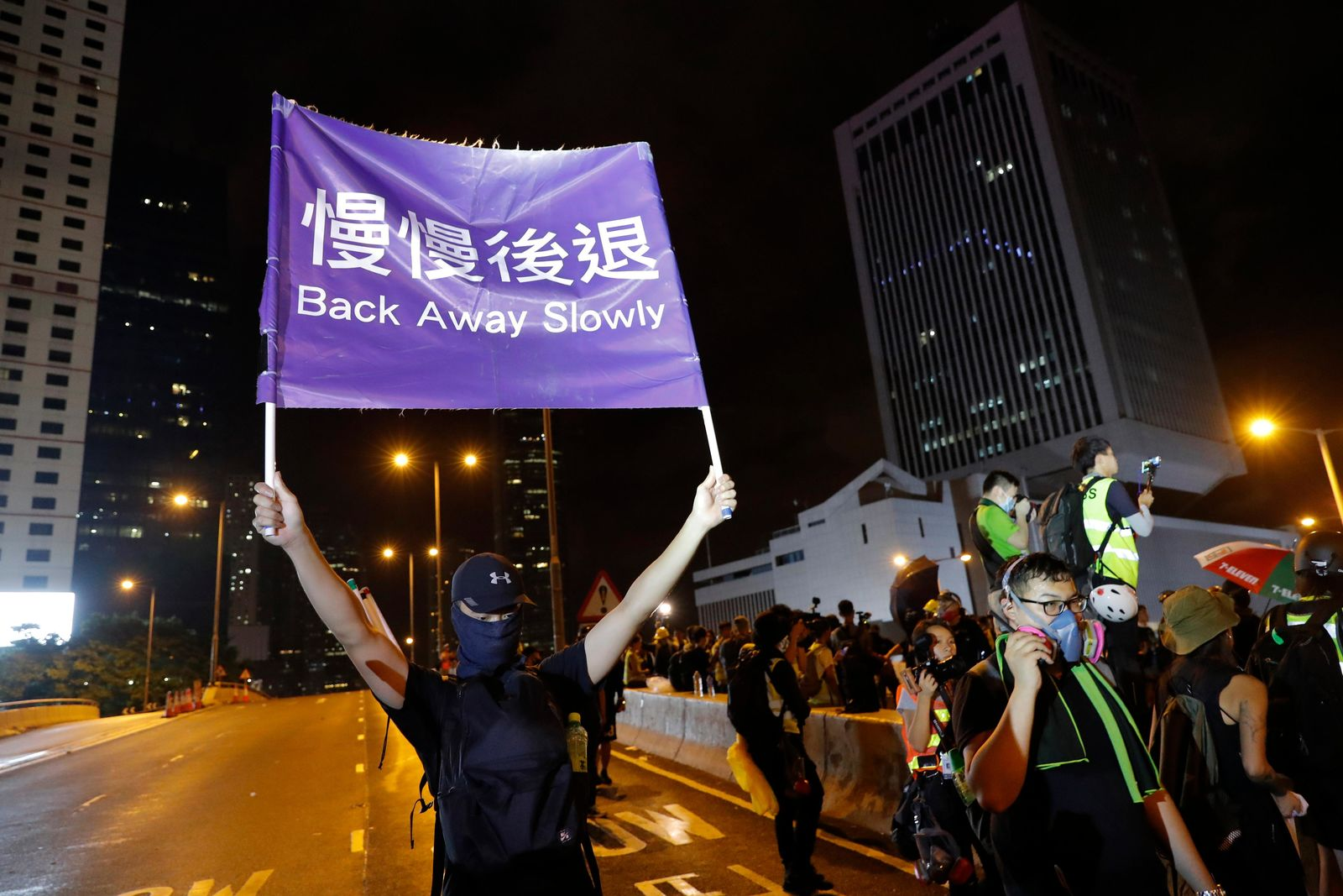 "A demonstrator holds up a sign reading ""Back away slowly"" to encourage other demonstrators to leave, near the Chinese Liaison Office in Hong Kong, Sunday, Aug. 18, 2019.{ } (AP Photo/Vincent Thian)"