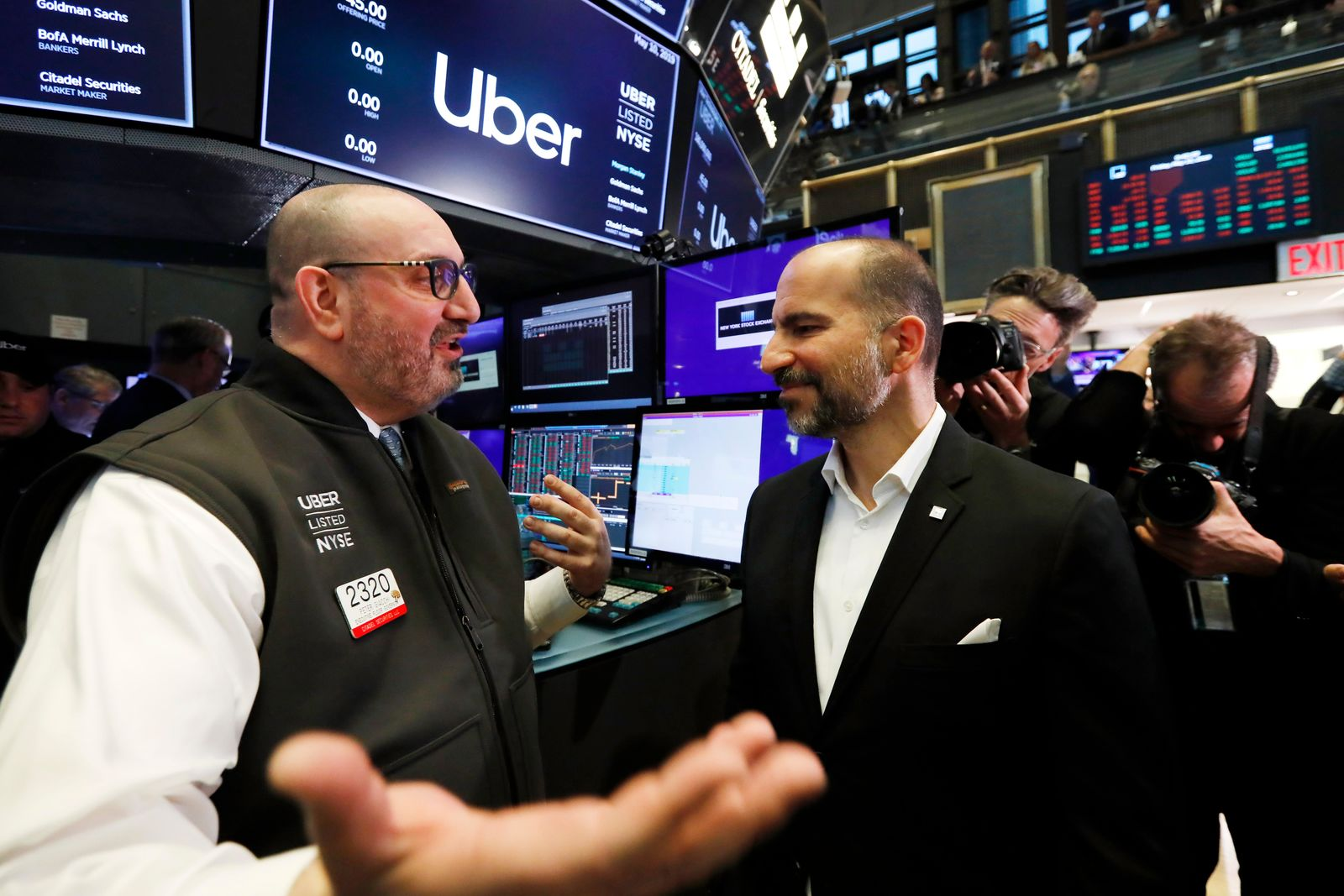 Uber CEO Dara Khosrowshahi, right, talks with specialist Peter Giacchi before his stock begins trading at the New York Stock Exchange, as his company makes its initial public offering, Friday, May 10, 2019. (AP Photo/Richard Drew)