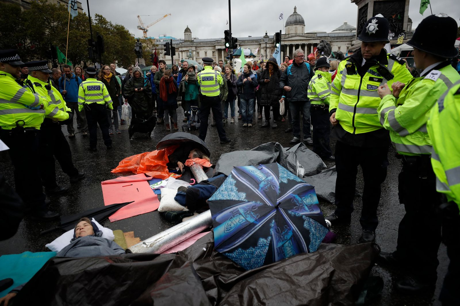 Extinction Rebellion climate change protesters lie with their arms locked together blocking a road at the bottom of Trafalgar Square in London, Friday, Oct. 11, 2019. Some hundreds of climate change activists are in London during a fifth day of protests by the Extinction Rebellion movement to demand more urgent actions to counter global warming. (AP Photo/Matt Dunham)