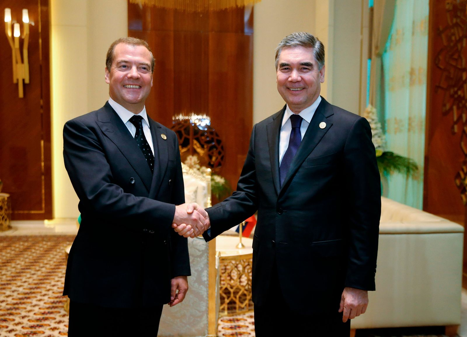 Russian Prime Minister Dmitry Medvedev, left, and Turkmenistan's President Gurbanguly Berdymukhamedov smile as they shake hands during the First Caspian Economic Forum in Turkmenbashi, Turkmenistan, Monday, Aug. 12, 2019. (Dmitry Astakhov, Sputnik, Government Pool Photo via AP)
