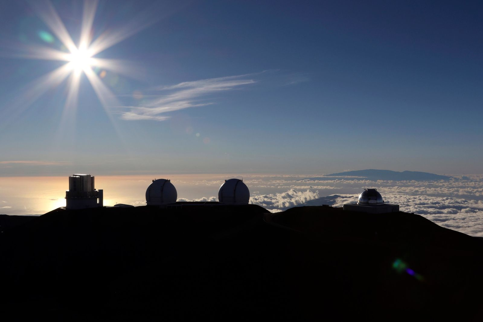 FILE - In this Sunday, July 14, 2019, file photo, the sun sets behind telescopes at the summit of Mauna Kea. Scientists are expected to explore fundamental questions about our universe when they use a giant new telescope planned for the summit of Hawaii's tallest mountain. That includes whether there's life outside our solar system and how stars and galaxies formed in the earliest years of the universe. But some Native Hawaiians don't want the Thirty Meter Telescope to be built at Mauna Kea's summit, saying it will further harm a place they consider sacred. (AP Photo/Caleb Jones, File)