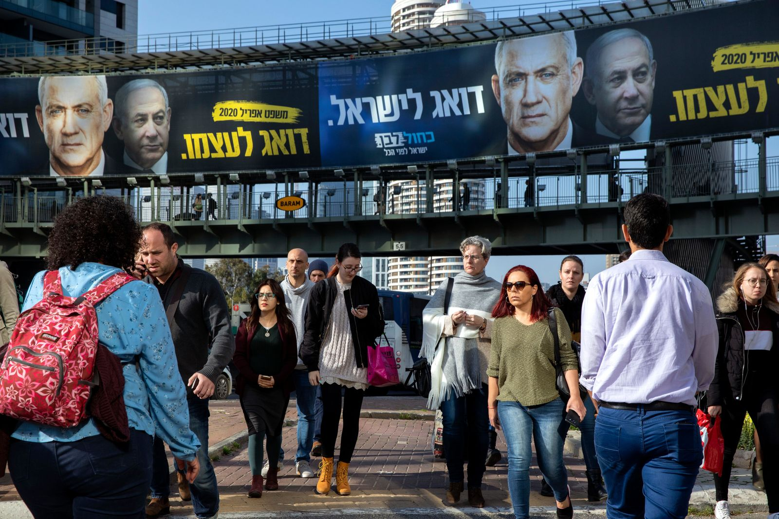 People walk next to an election campaign billboard of Blue and White party shows its party leader Benny Gantz, and Israeli Prime Minister Benjamin Netanyahu, in Ramat Gan, Israel, Tuesday, Feb. 18, 2020. (AP Photo/Oded Balilty)