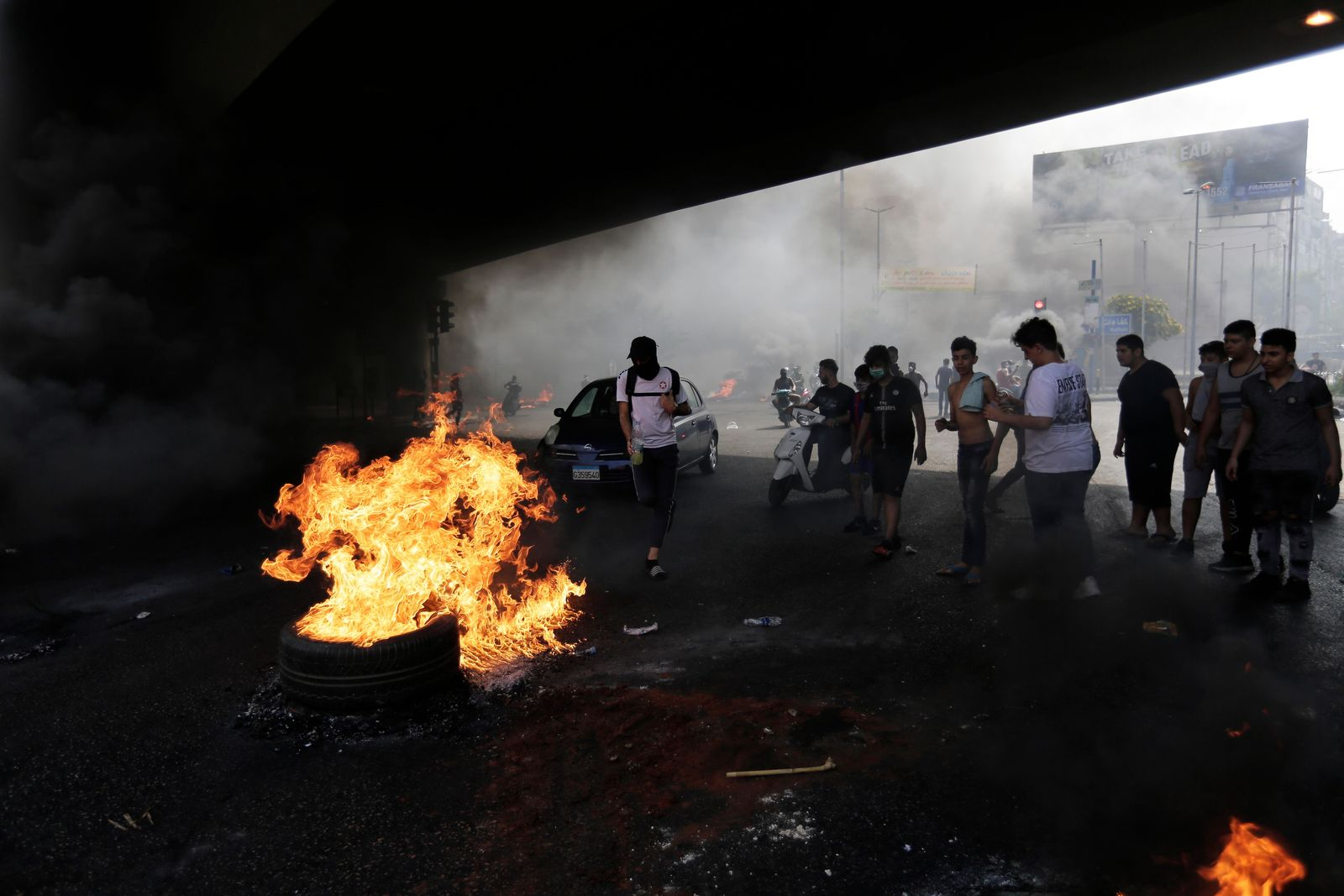 Anti-government protesters set fire on tires to block a road during a protest against government's plans to impose new taxes in Beirut, Lebanon, Friday, Oct. 18, 2019.{ } (AP Photo/Hassan Ammar)