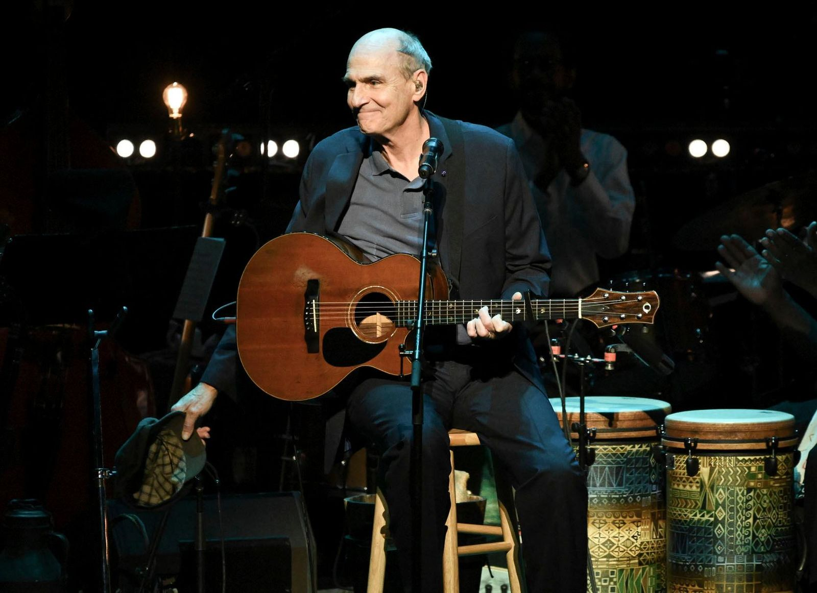 "FILE - This Nov. 7, 2018 file photo shows James Taylor performing at JONI 75: A Birthday Celebration in Los Angeles. Taylor has a deal with the producer-distributor Audible for the audio-only ""Break Shot,"" focusing on his early years and end on ""the cusp"" of his 1970s fame. Scheduled for early 2020, the book features an interview with journalist Bill Flanagan and highlights from his music. (Photo by Richard Shotwell/Invision/AP, File)"