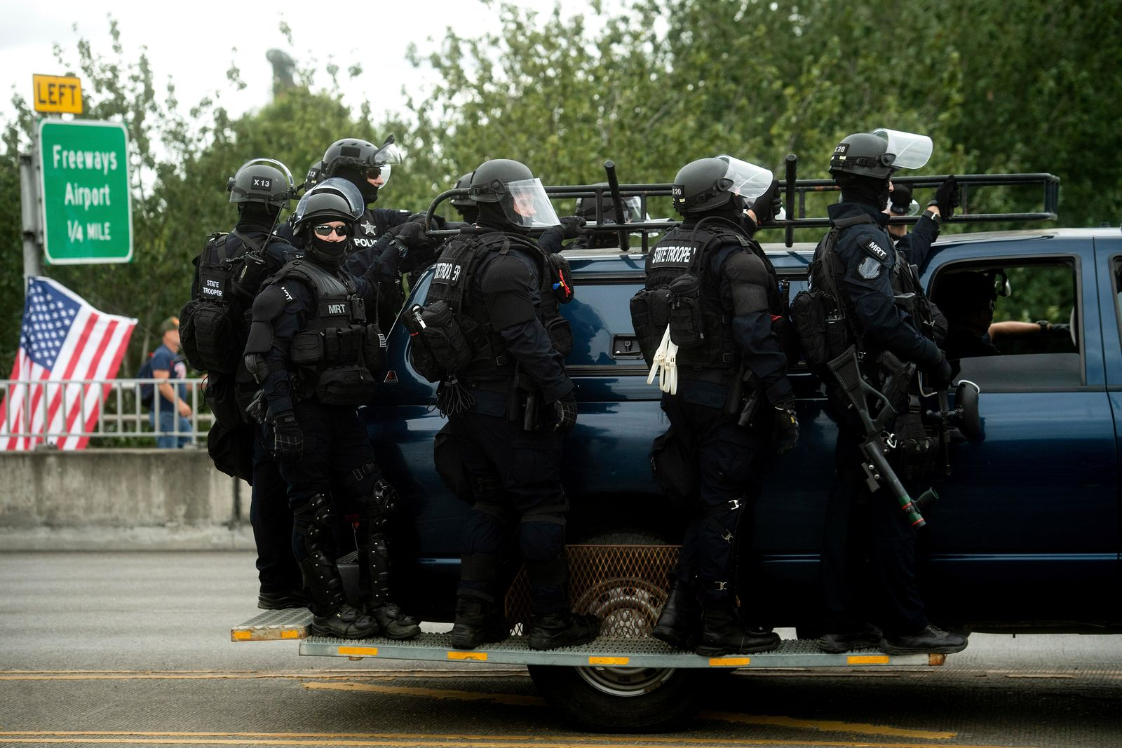 "Police officers ride on the side of a vehicle as right-wing demonstrators and counter-protesters gather in Portland, Ore., for an ""End Domestic Terrorism"" rally on Saturday, Aug. 17, 2019.   Right-wing groups and counterprotesters gathered in downtown Portland and authorities set up concrete barriers and closed streets in an effort to contain the two groups.(AP Photo/Noah Berger)"