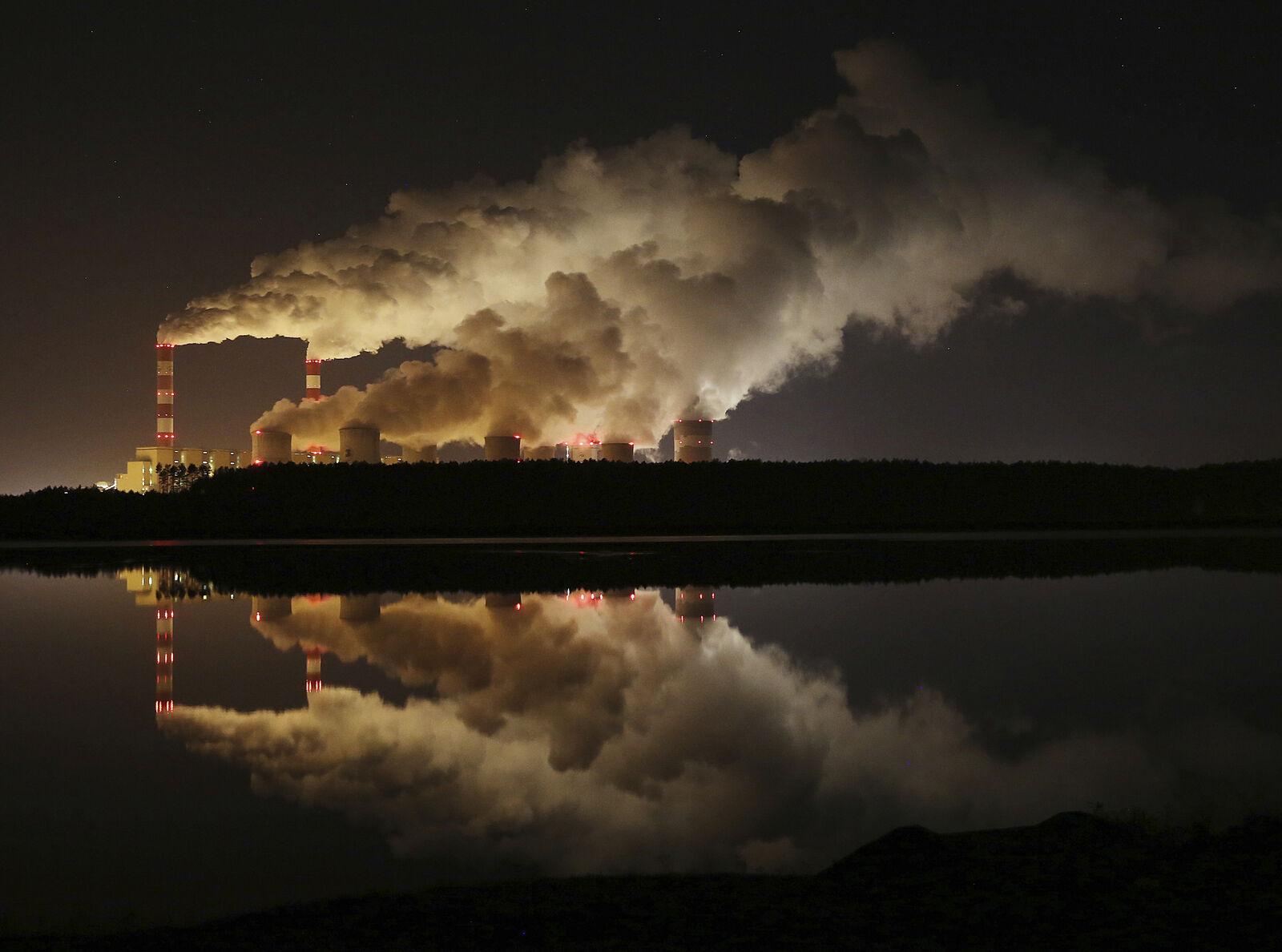 FILE - In this Wednesday, Nov. 28, 2018 file photo, clouds of smoke over Europe's largest lignite power plant in Belchatow, central Poland. Greenhouse gas emissions in the European Union have been reduced by 24% compared to 1990 levels, according to the bloc's annual climate report. (AP Photo/Czarek Sokolowski, file)