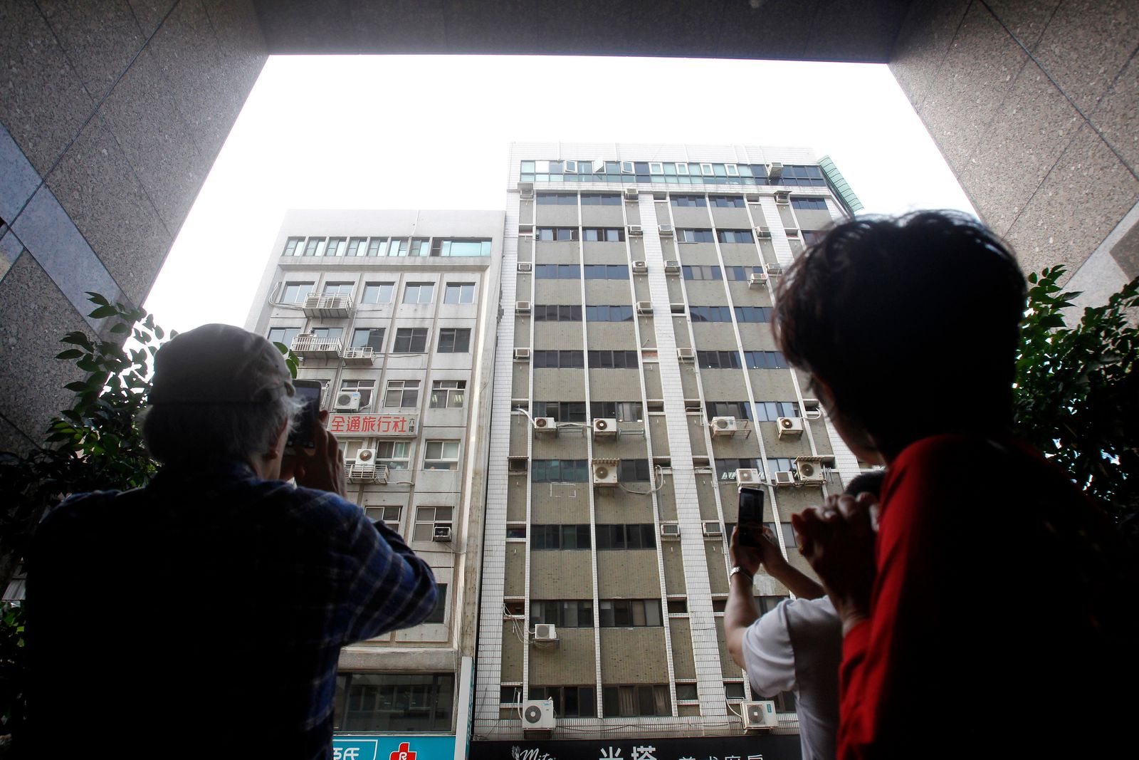 People take photos of buildings damaged by an earthquake in Taipei, Taiwan, Thursday, April 18, 2019.n. (AP Photo/Chiang Ying-ying)