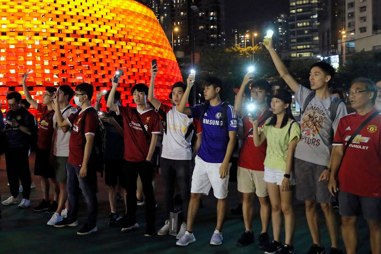Pro-democracy football fans gather to form a human chain as they sing songs at Victoria Park in Hong Kong, Wednesday, Sept. 18, 2019. (AP Photo/Kin Cheung)