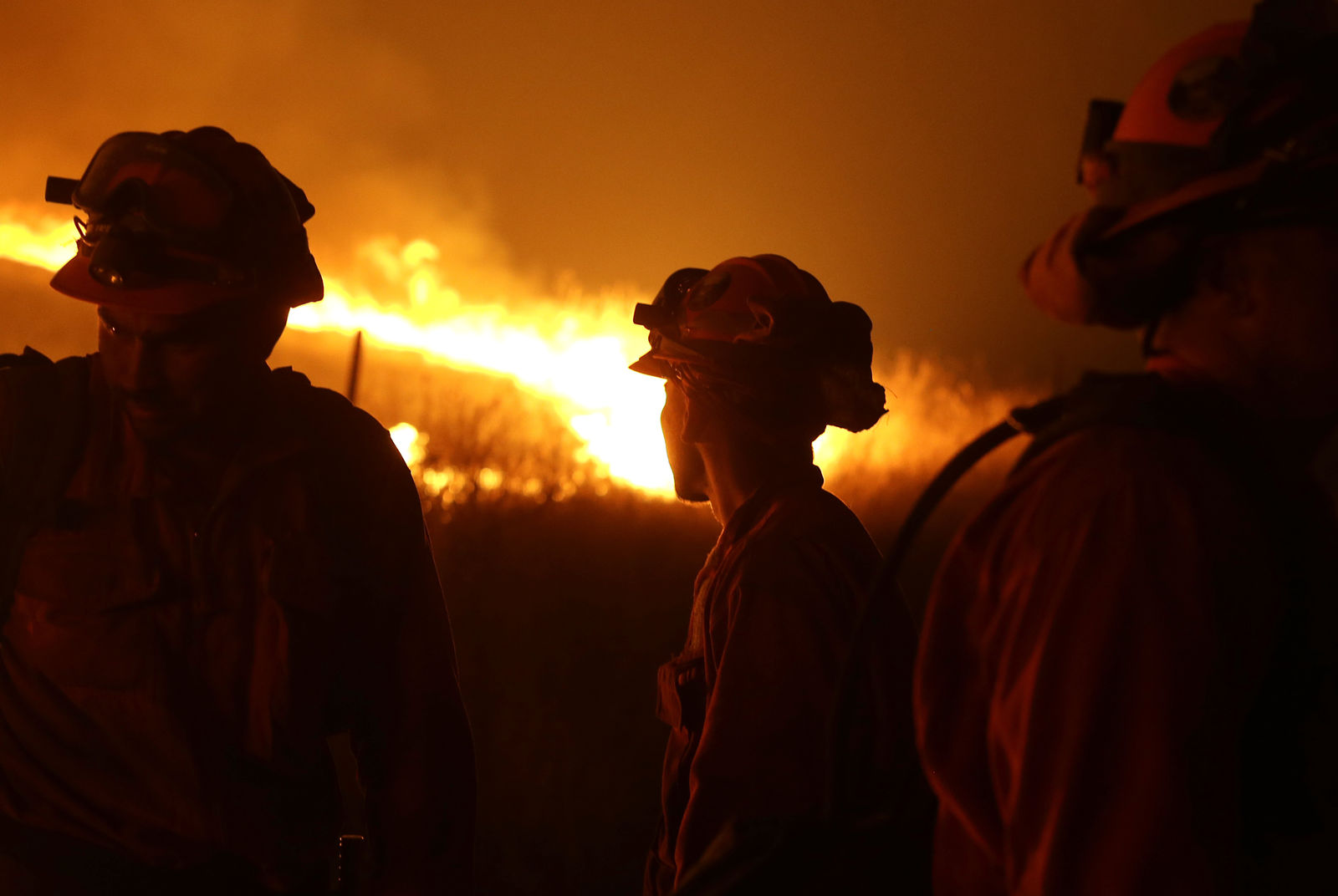 FILE - In this Sept. 12, 2015 file photo, California Department of Corrections and Rehabilitation inmates stand guard as flames from the Butte Fire approach a containment line near San Andreas, Calif. Attorneys representing 14 local governments said Tuesday, June 18, 2019 that they had reached a $1 billion settlement with California utility Pacific Gas & Electric for a series of fires dating to 2015. (AP Photo/Rich Pedroncelli, File)