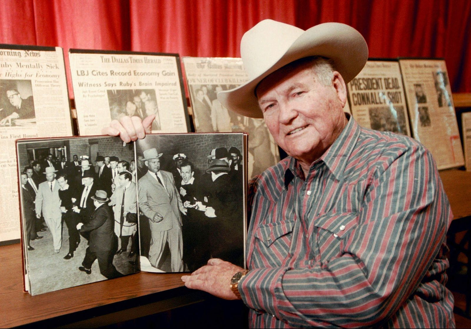 FILE - In this Dec. 11, 1998 file photo, shows Jim Leavelle in Stafford, Kansas holding the iconic 1963 photograph, as he escorted Lee Harvey Oswald moments before he is shot in Dallas.  Leavelle, the longtime Dallas lawman has died, Thursday, Aug. 29, 2019. He was 99.  (Sandra J. Milburn/The Hutchinson News via AP)