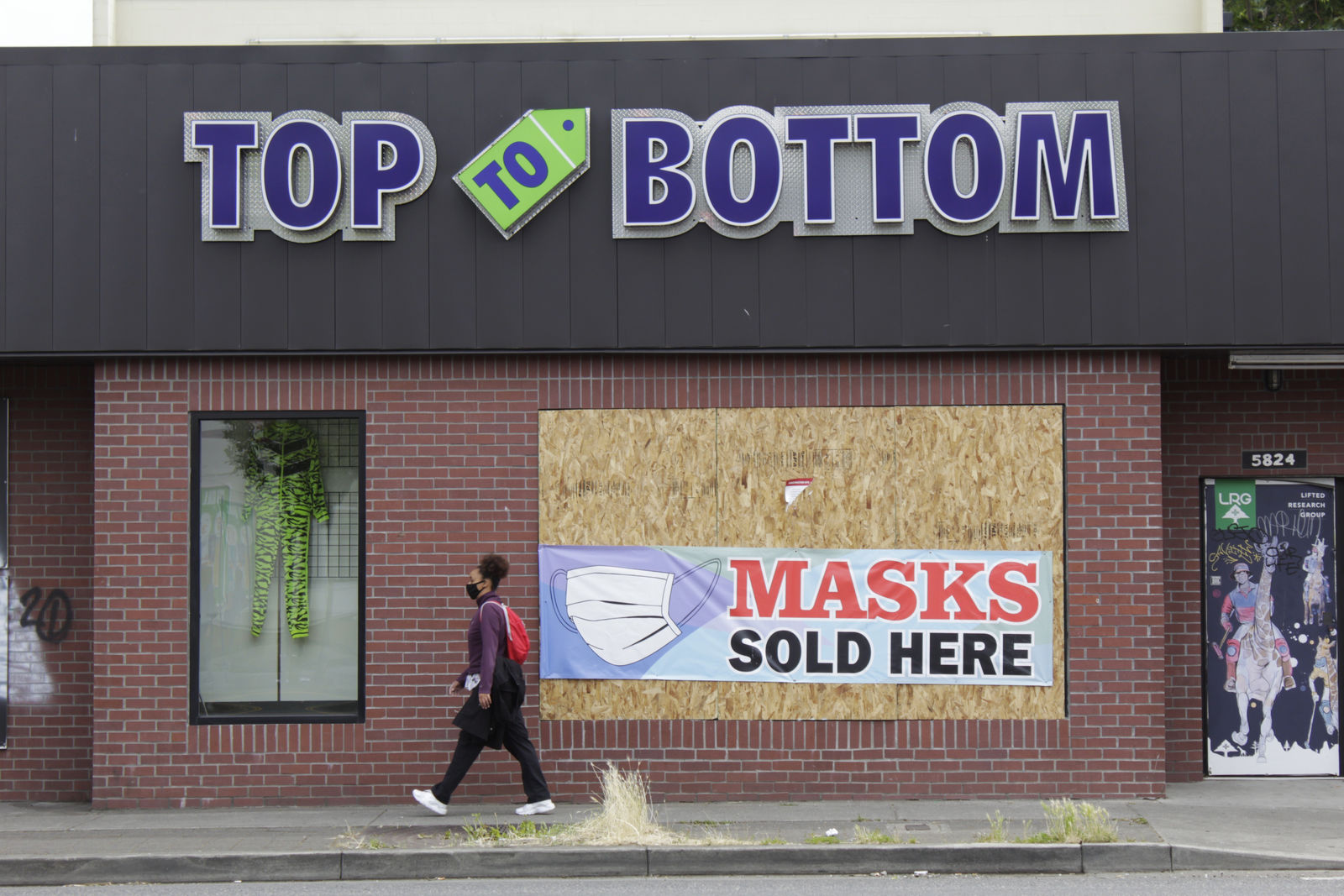A pedestrian walks past a business damaged during recent protests on Wednesday, July 1, 2020, in North Portland, a historically Black neighborhood in Oregon. (AP Photo/Gillian Flaccus)