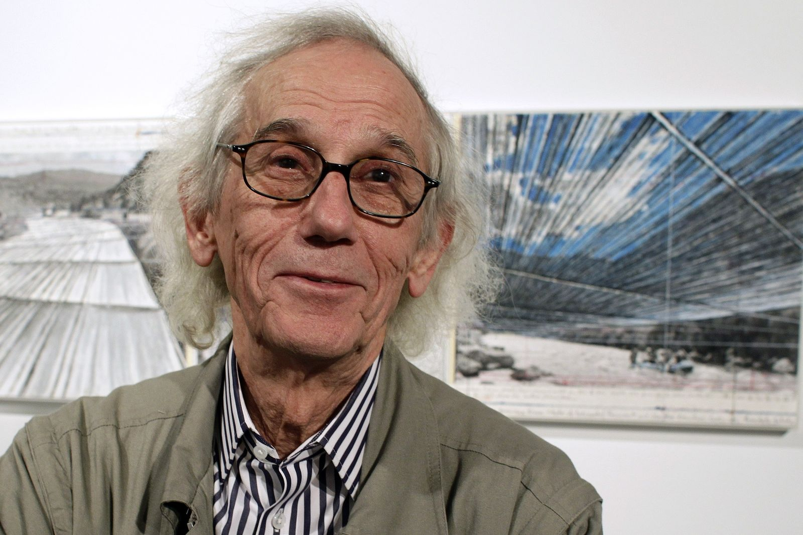 "FILE - This Jan. 23, 2013 file photo shows artist Christo posing in front of his proposed ""Over the River"" project at the Metropolitan State University Center for Visual Art in Denver. (AP Photo/Brennan Linsley, file)"