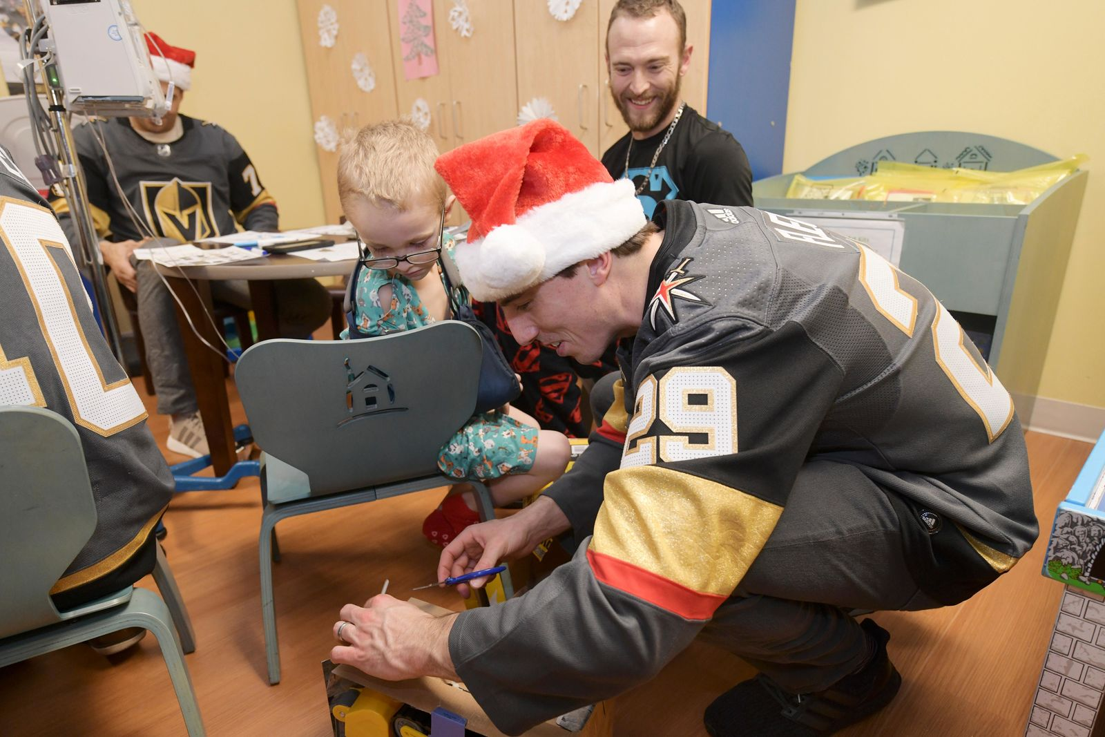 Marc-Andre Fleury helps Brayden Pena open a gift during a visit of the Golden Knights to Summerlin Hospital Friday, December 21, 2018. CREDIT: Sam Morris/Las Vegas News Bureau