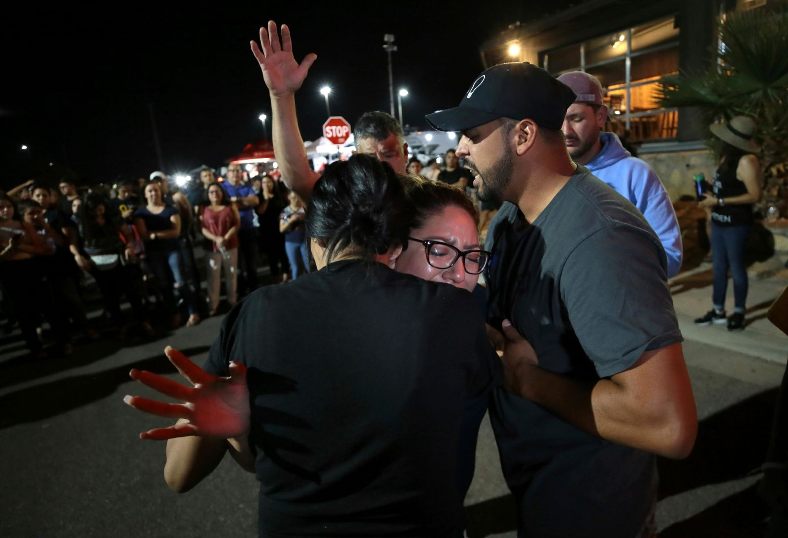 A woman is overcome with emotion as members of the Iglesia Cristiana Manatial en el Desierto pray for her at a memorial Monday, Aug. 5, 2019, outside the Walmart in El Paso, Texas, where a mass shooting took place on Saturday. (Mark Lambie/The El Paso Times via AP)