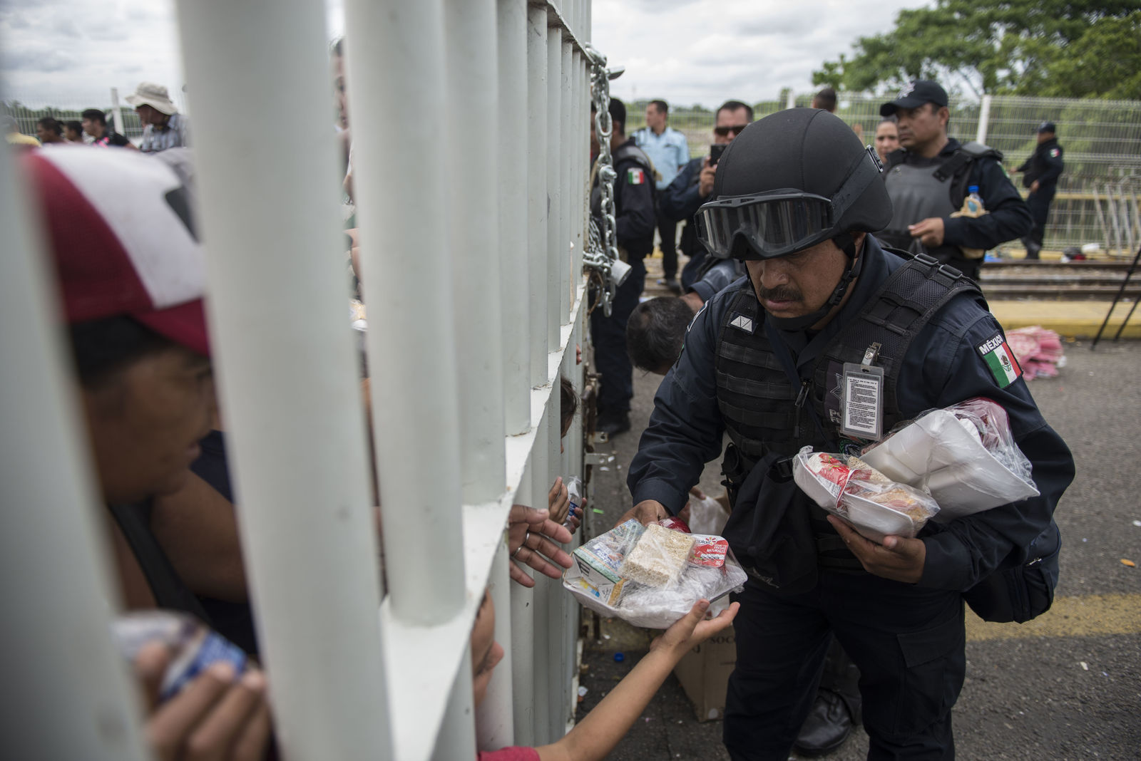 A Mexican Federal Police officer hands out food to Honduran migrants stuck in no man's land on the bridge over the Suchiate River that is the border between Guatemala and Mexico, near Ciudad Hidalgo, Mexico, Saturday, Oct. 20, 2018. (AP Photo/Oliver de Ros)