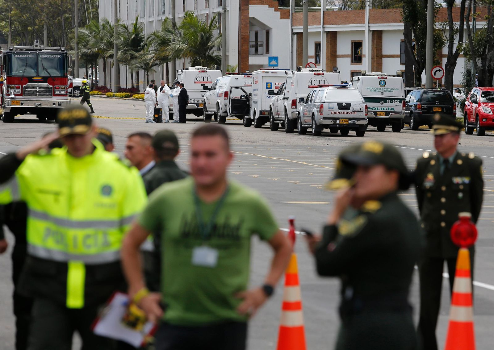 Forensic workers, behind top, work the scene of a deadly car bombing at the General Santander police academy in Bogota, Colombia, Thursday, Jan. 17, 2019. (AP Photo/John Wilson Vizcaino)