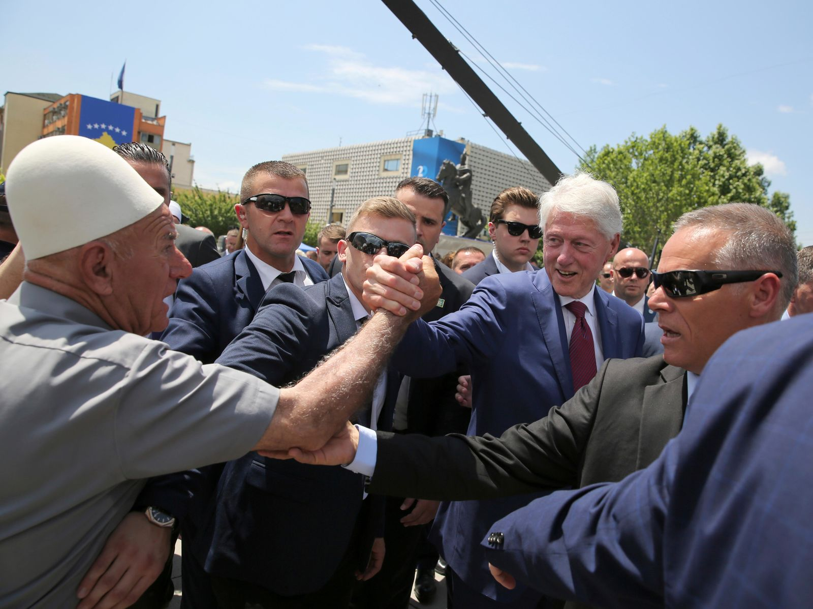 Former U.S. President Bill Clinton, center right, shakes hands with an elderly ethnic Albanian wears his traditional cap during anniversary celebrations in the capital Pristina, Kosovo, Wednesday, June 12, 2019.{ } (AP Photo/Visar Kryeziu)