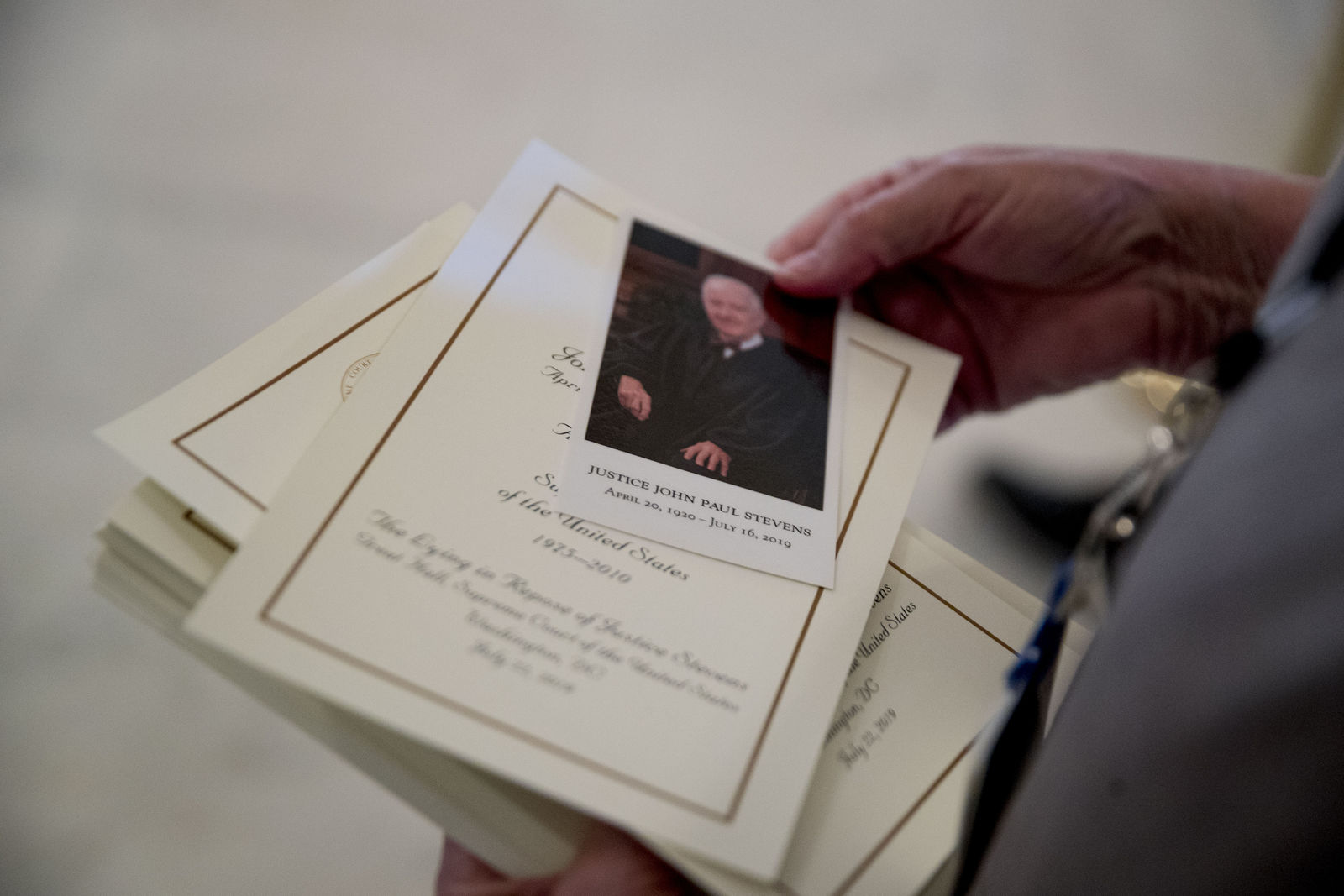 Visitors are handed a photograph and information as they pay their respects for the late Supreme Court Justice John Paul Stevens as he lies in repose in the Great Hall of the Supreme Court in Washington, Monday, July 22, 2019. (AP Photo/Andrew Harnik)