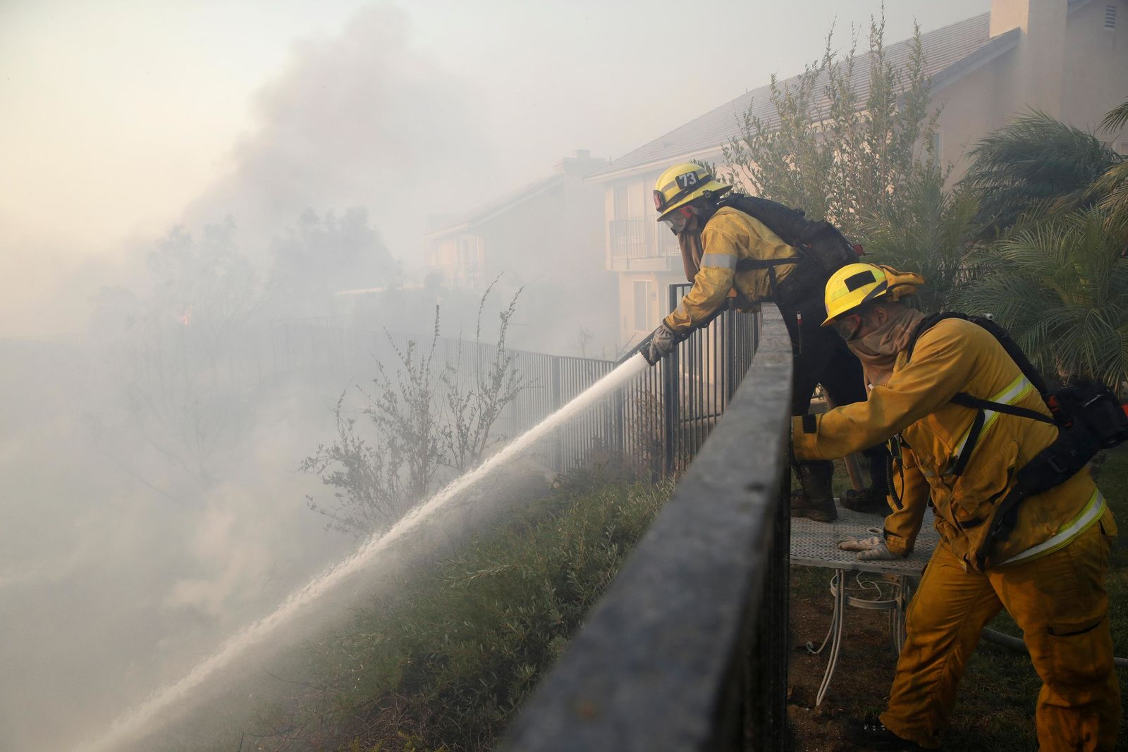 Firefighters make a stand on an advancing wildfire from the backyard of a home Friday, Oct. 11, 2019, in Porter Ranch, Calif. (AP Photo/Marcio Jose Sanchez)