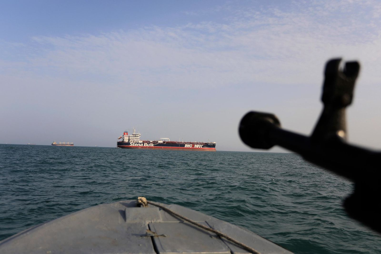 In this Sunday, July 21, 2019 photo, a speedboat of Iran's Revolutionary Guard trains a weapon toward the British-flagged oil tanker Stena Impero, which was seized in the Strait of Hormuz on Friday by the Guard, in the Iranian port of Bandar Abbas.{ } (Morteza Akhoondi/Tasnim News Agency via AP)