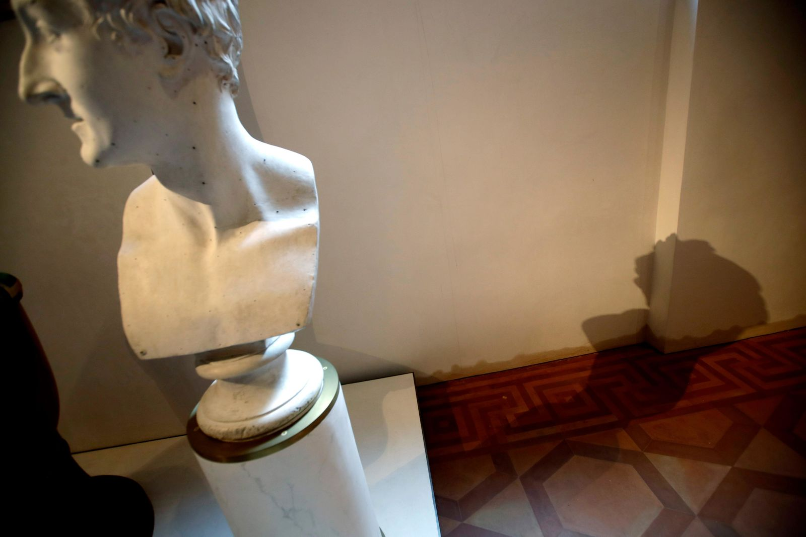 The 'Bust of Leopoldo Cicognara' by Antonio Canova casts its shadow against a wall showing a dark stain indicating the level the water reached during the latest high tide flooding, at the Accademia Gallery, in Venice, Saturday, Nov. 16, 2019. As high tidal waters returned to Venice on Saturday, four days after the city experienced its worst flooding in 50 years, young Venetians are responding to the worst flood in their lifetimes by volunteering to help salvage manuscripts, clear out waterlogged books and lend a hand where needed throughout the stricken city. (AP Photo/Luca Bruno)