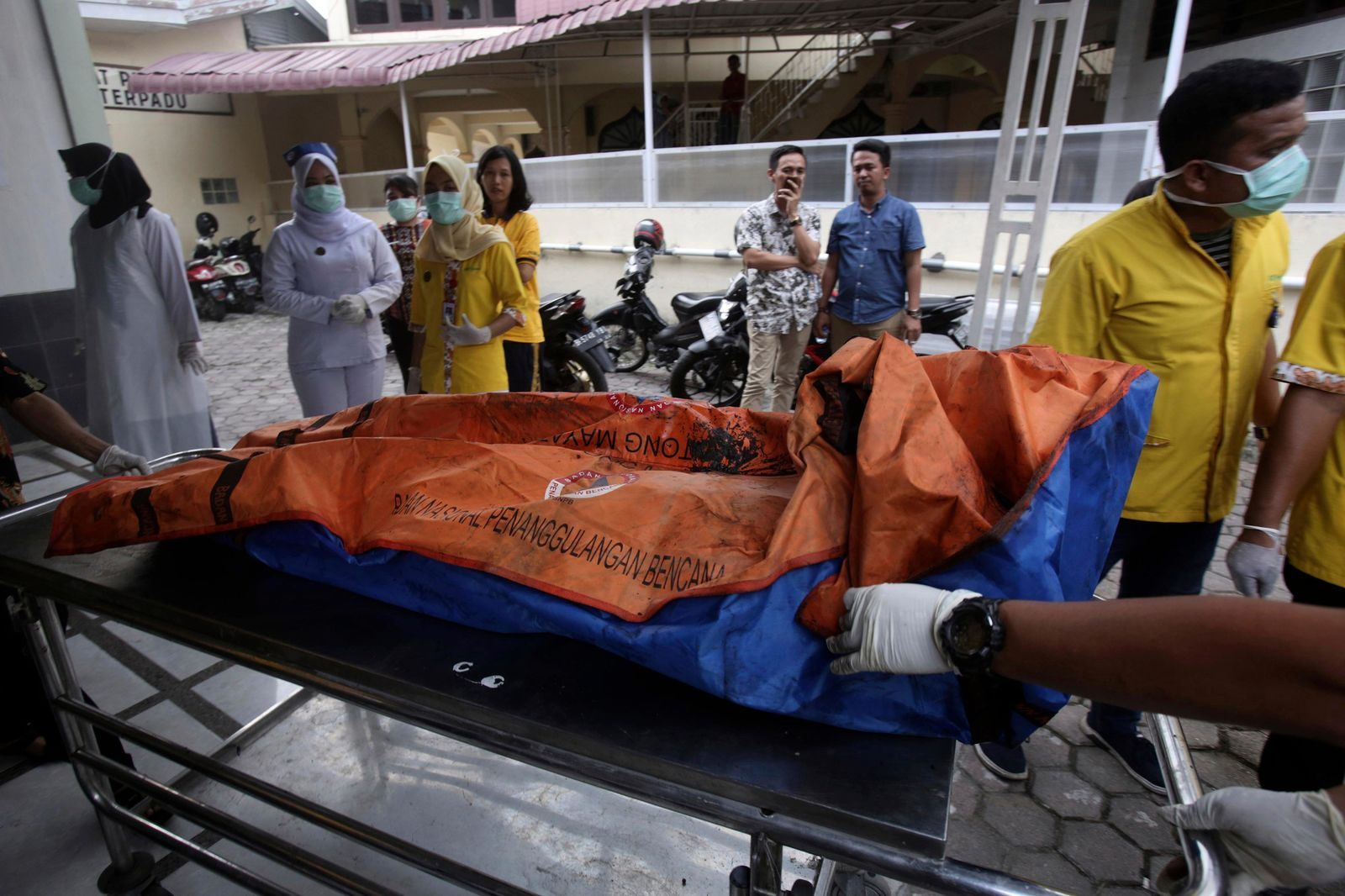 Paramedics put body bags containing the remains of the victims of a fire that razed through a match factory on a stretcher upon arrival at a hospital in Medan, North Sumatra, Indonesia, Friday, June 21, 2019. A number of people including children were killed in the fire that swept through a house that doubled as a match factory, a disaster official said Friday. (AP Photo/Binsar Bakkara)