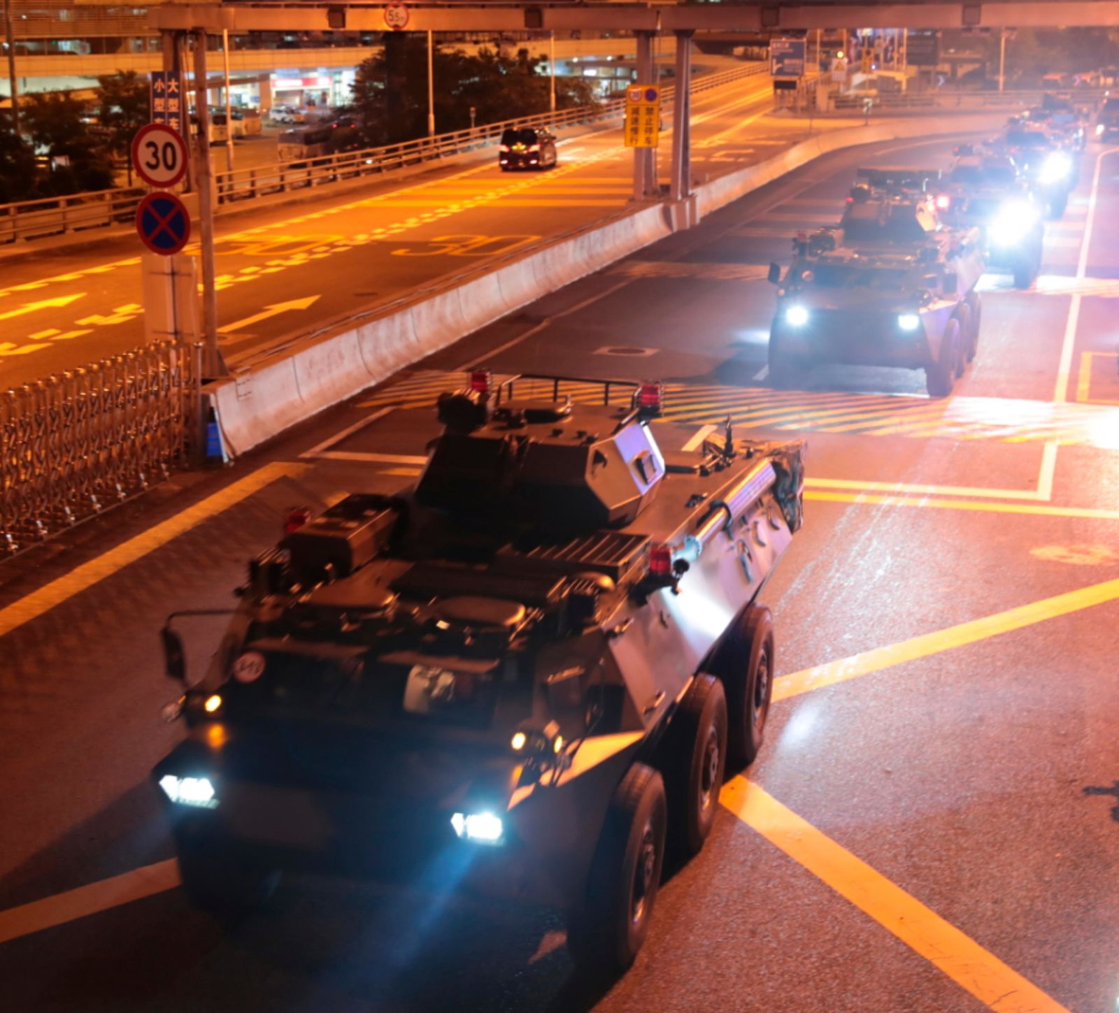 In this photo released by China's Xinhua News Agency, armored personnel carriers of China's People's Liberation Army (PLA) pass through the Huanggang Port border between China and Hong Kong, Thursday, Aug. 29, 2019. (Yuan Junmin/Xinhua via AP)