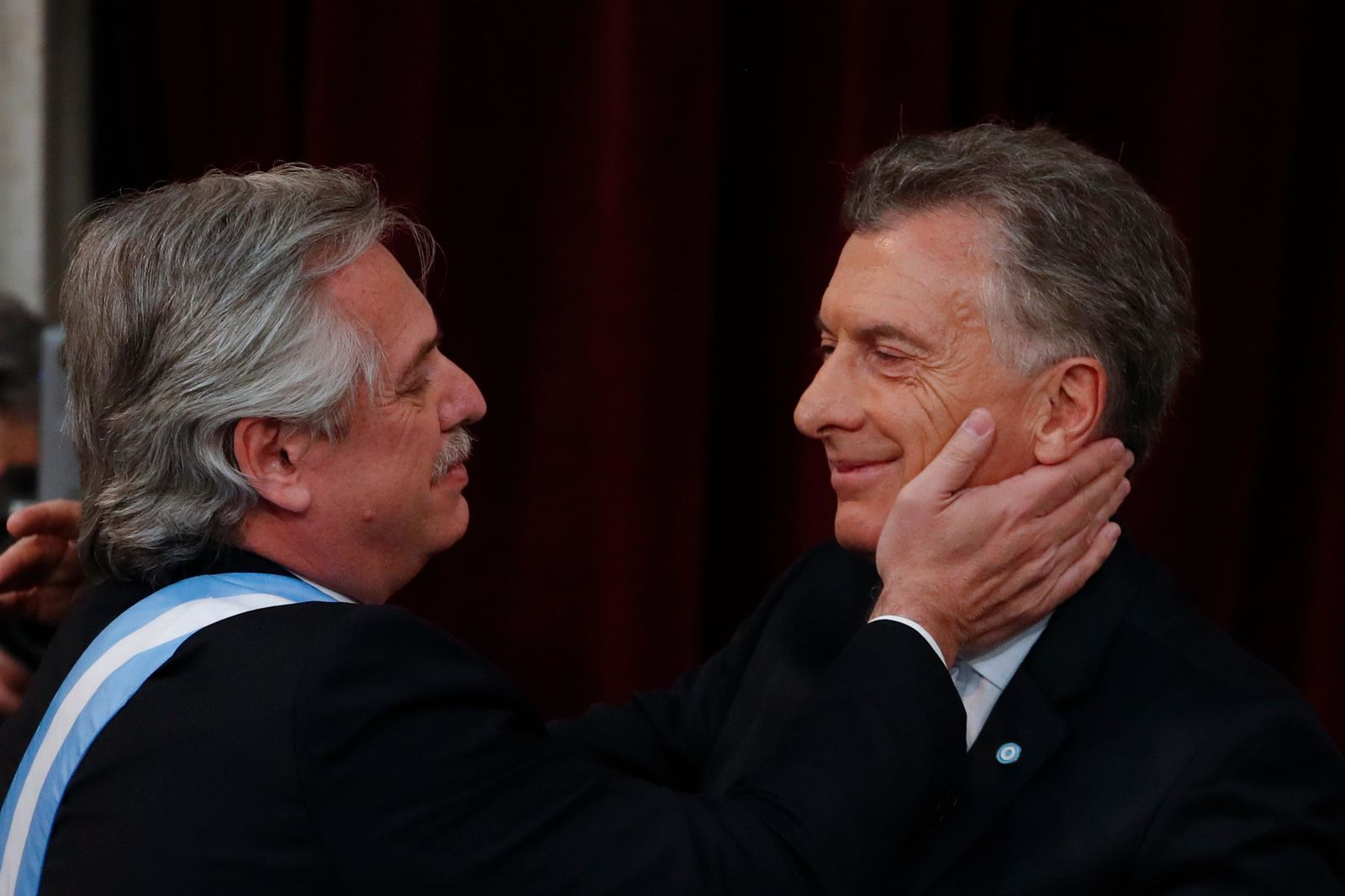 Argentina's new President Alberto Fernandez, left, greets outgoing president Mauricio Macri after taking the oath of office at the Congress in Buenos Aires, Argentina, Tuesday, Dec. 10, 2019. (AP Photo/Natacha Pisarenko)