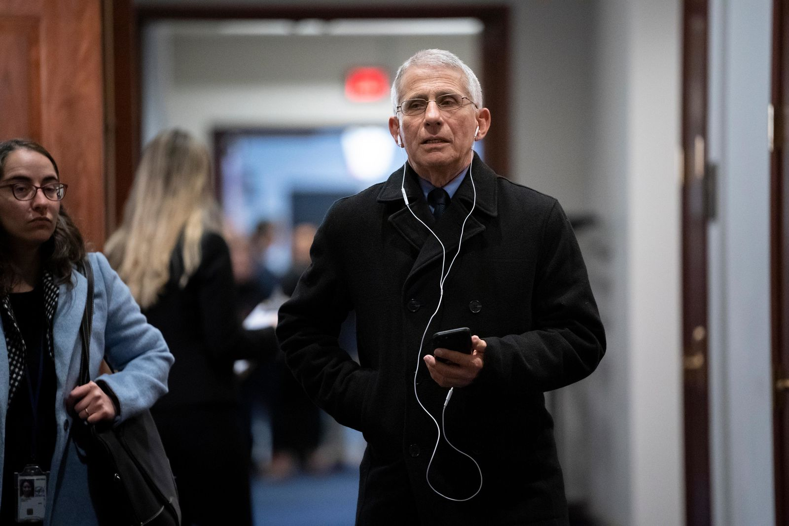 Anthony Fauci, director of the National Institute of Allergy and Infectious Diseases, takes a phone call outside a room on Capitol Hill where he and others from the president's coronavirus task force briefed members of the House of Representatives on the outbreak of the new respiratory virus sweeping the globe, in Washington, Friday, Feb. 28, 2020. (AP Photo/J. Scott Applewhite)