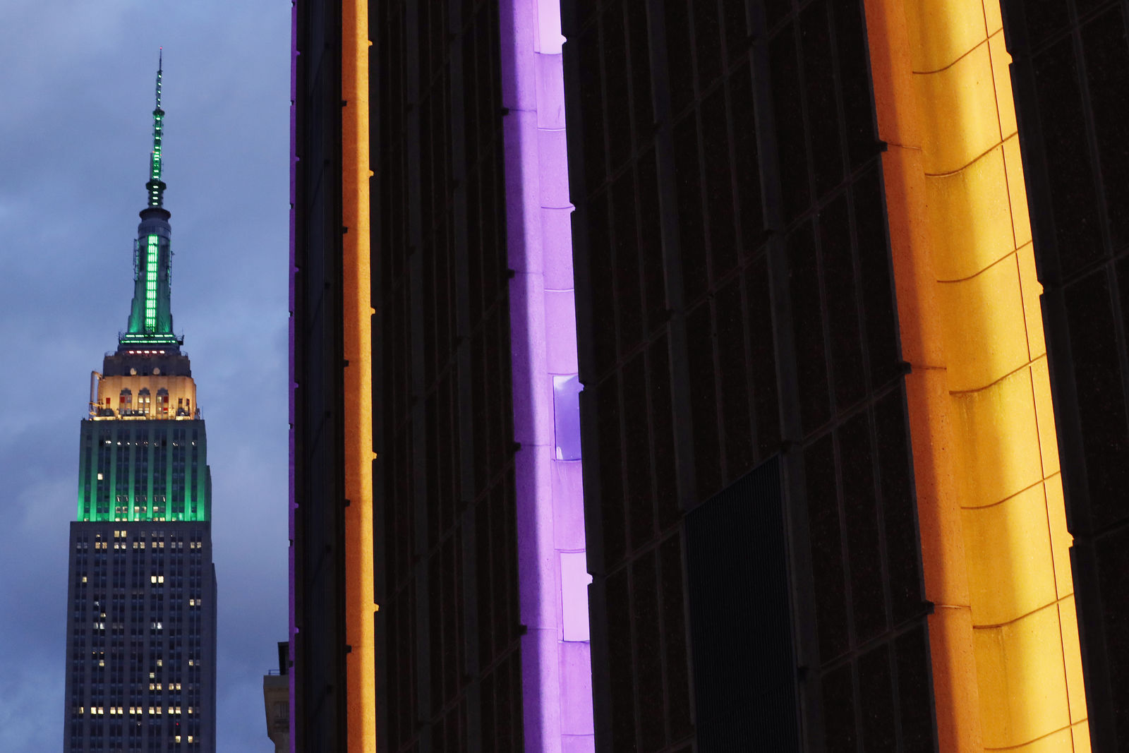 The exterior of Madison Square Garden, right, is colored orange and purple, as the Empire State Building in the wak of the death of retired NBA star Kobe Bryant before the start of a basketball game between the Brooklyn Nets and the New York Knicks, Sunday, Jan. 26, 2020, in New York. (AP Photo/Kathy Willens)