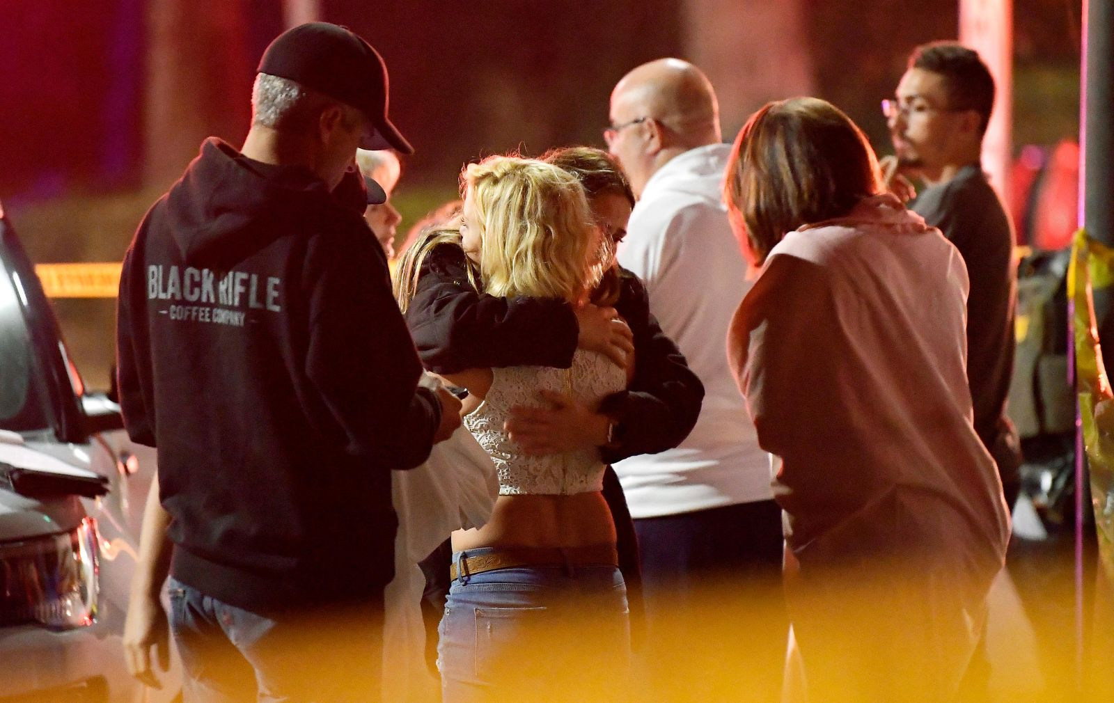 "People comfort each other as they stand near the scene Thursday, Nov. 8, 2018, in Thousand Oaks, Calif., where a gunman opened fire Wednesday inside a country dance bar crowded with hundreds of people on ""college night."" (AP Photo/Mark J. Terrill)"