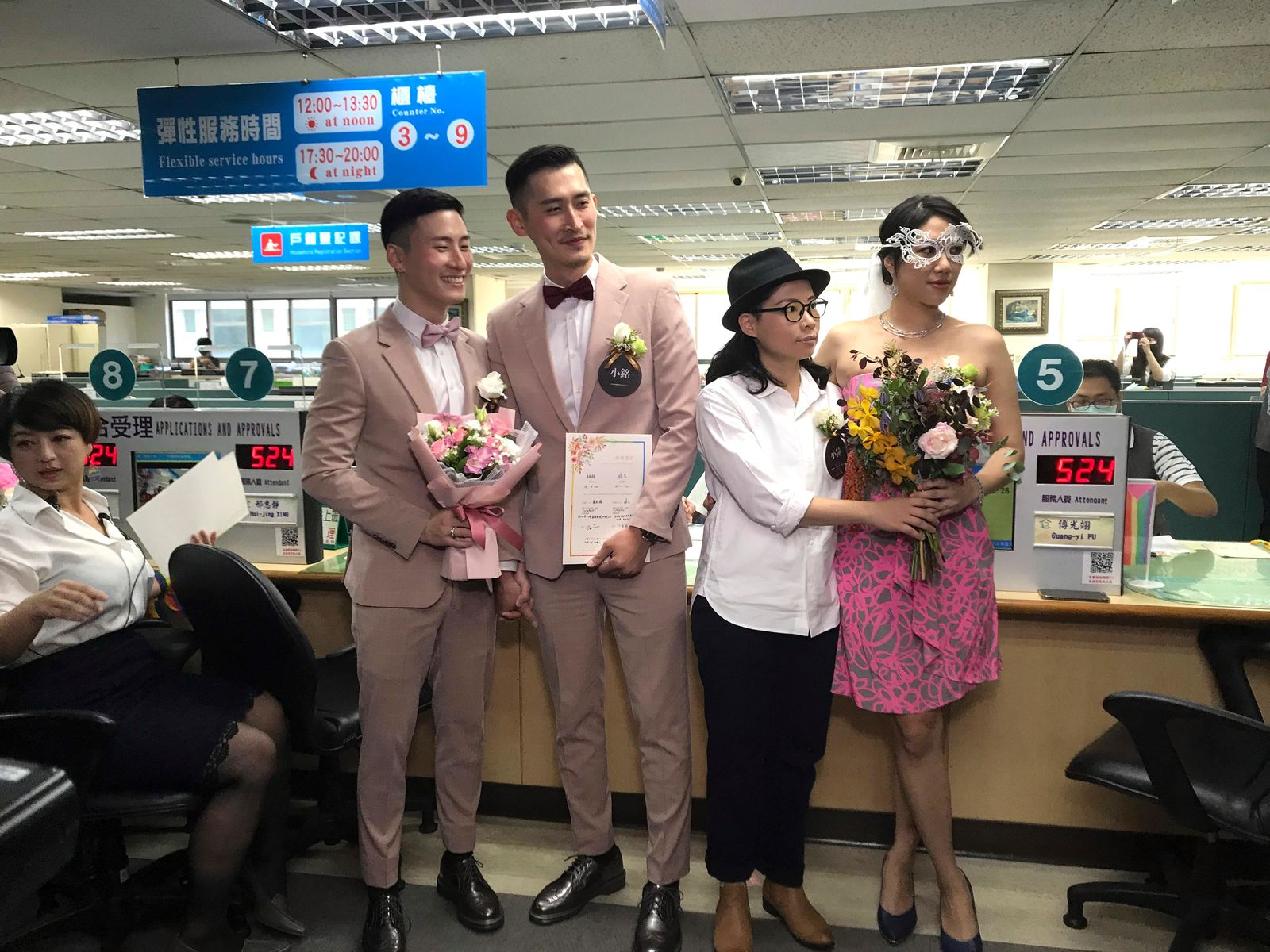 Two same-sex couples pose for a photo at the household registration office to register their legal marriage in Xingyi District in Taipei, Taiwan, Friday, May 24, 2019.{ } (AP Photo/Johnson Lai)