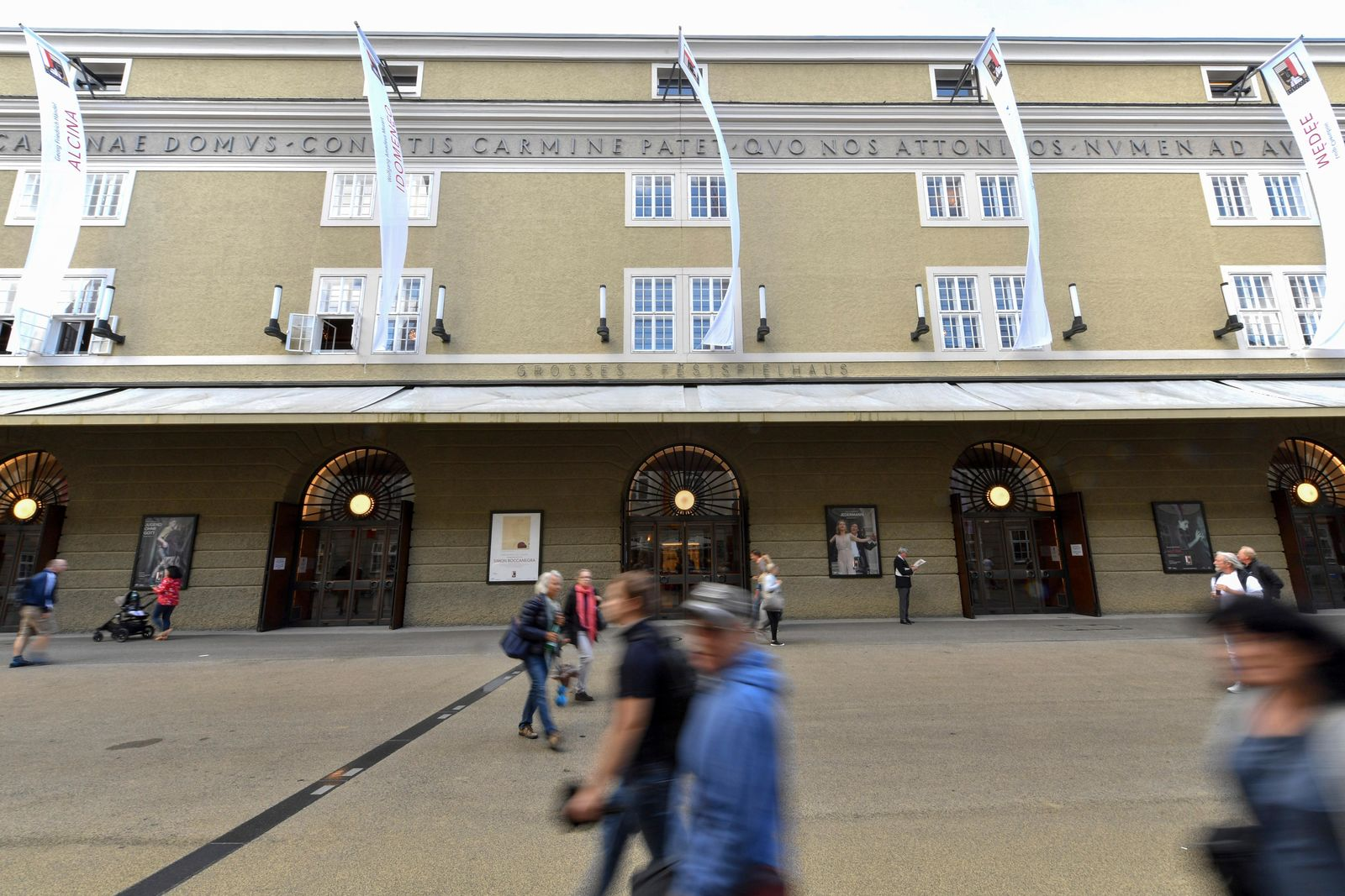 FILE - In this Aug. 14, 2019, file photo, people walk by the opera house in Salzburg, Austria, where singer Placido Domingo is scheduled to perform 'Luisa Miller' by Giuseppe Verdi. Domingo is scheduled to appear onstage at the Salzburg Festival Aug. 25, 2019, to perform for the first time since multiple women have accused the opera legend of sexual harassment in allegations brought to light by The Associated Press. (AP Photo/Kerstin Joensson, File)