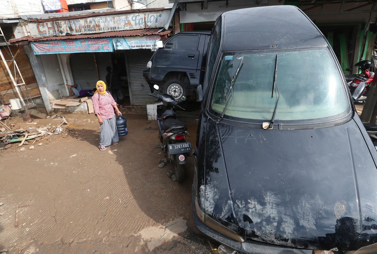 A women stands near the wreckage of cars that were swept away by flood in Bekasi, West Java, Indonesia, Friday, Jan. 3, 2020.{ } (AP Photo/Achmad Ibrahim)
