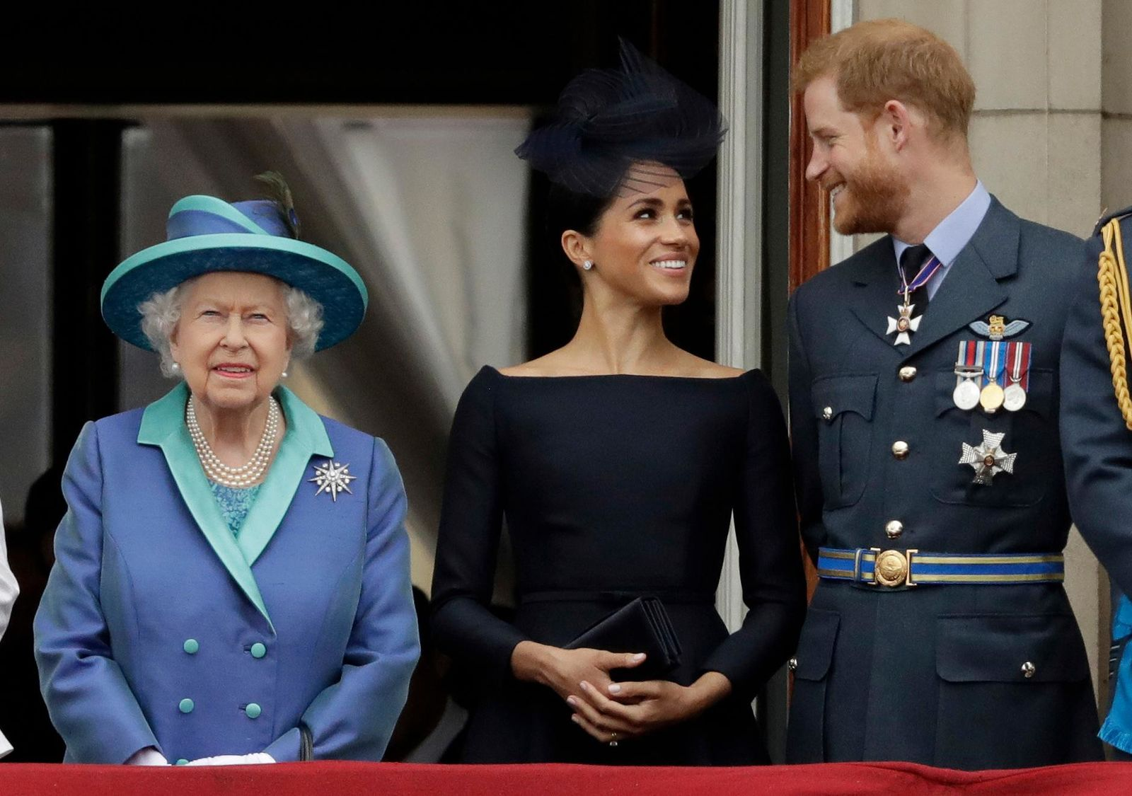"FILE - In this Tuesday, July 10, 2018 file photo Britain's Queen Elizabeth II, and Meghan the Duchess of Sussex and Prince Harry watch a flypast of Royal Air Force aircraft pass over Buckingham Palace in London. As part of a surprise announcement distancing themselves from the British royal family, Prince Harry and his wife Meghan declared they will ""work to become financially independent"" _ a move that has not been clearly spelled out and could be fraught with obstacles. (AP Photo/Matt Dunham, File)"