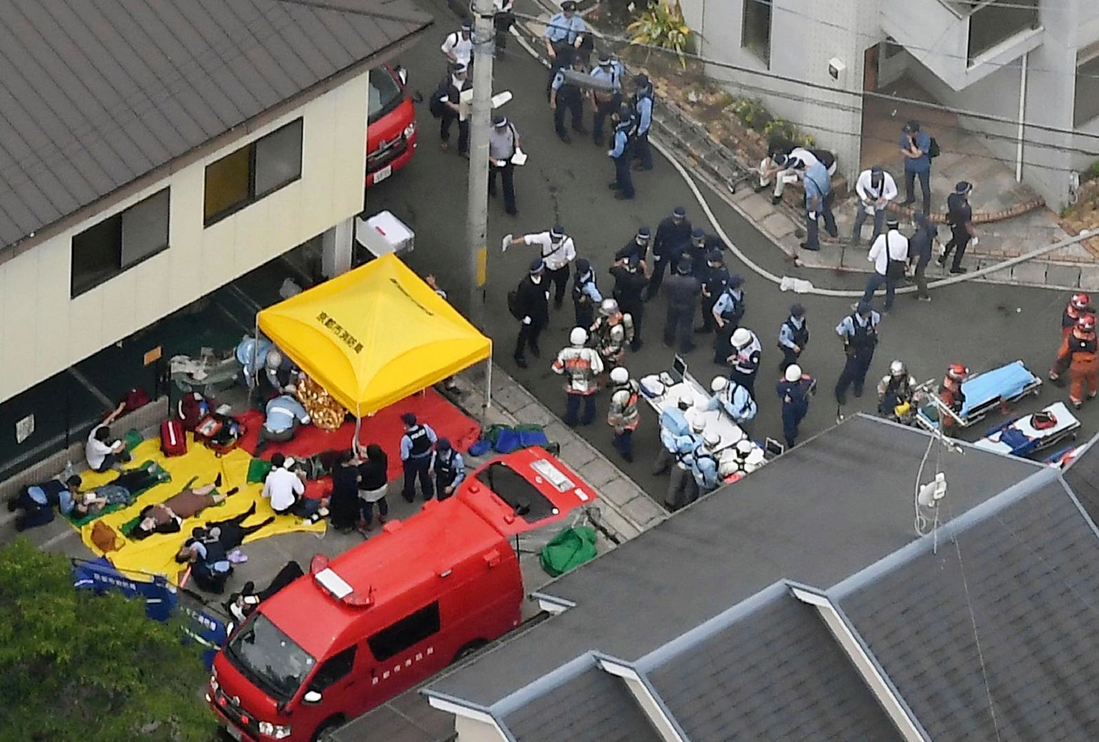 People injured in a fire are treated near a Kyoto Animation building in Kyoto, western Japan, Thursday, July 18, 2019. (Kyodo News via AP)