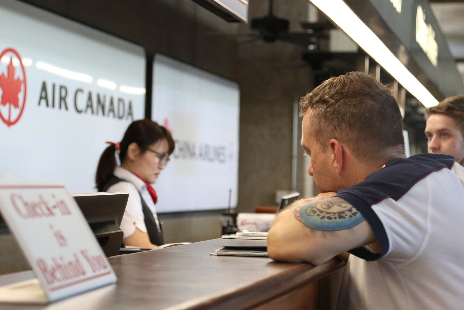 Andrew Szucs, right, who was on the Air Canada flight that made an emergency landing, waits for assistance at the Air Canada desk, Thursday, July 11, 2019 at Honolulu's international airport. (AP Photo/Caleb Jones)